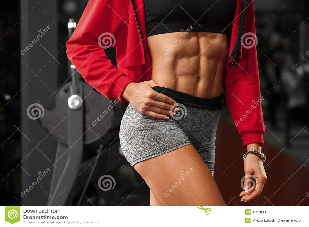 Fitness woman showing abs and flat belly in gym. Beautiful athletic girl, shaped abdominal, slim waist