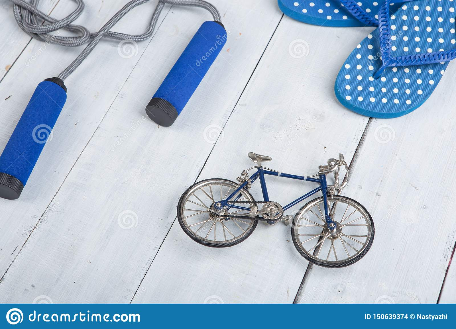 Fitness/sport and healthy lifestyle concept - Jumping/skipping rope with blue handles, flip flops in polka dots and model of