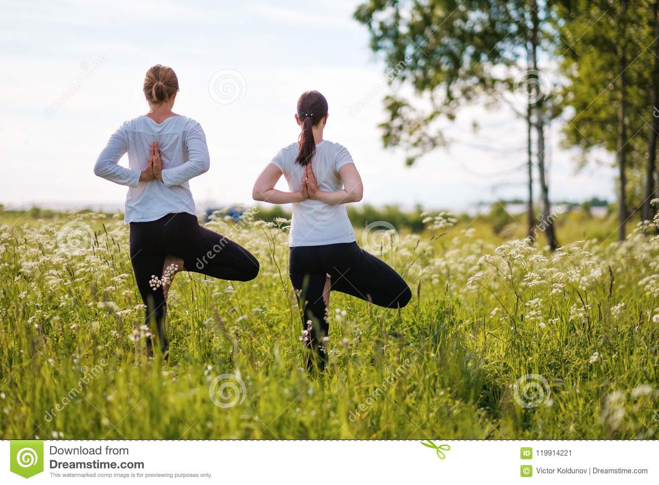 Two Women Le Doing Yoga Exercises, Standing On One Leg At ...