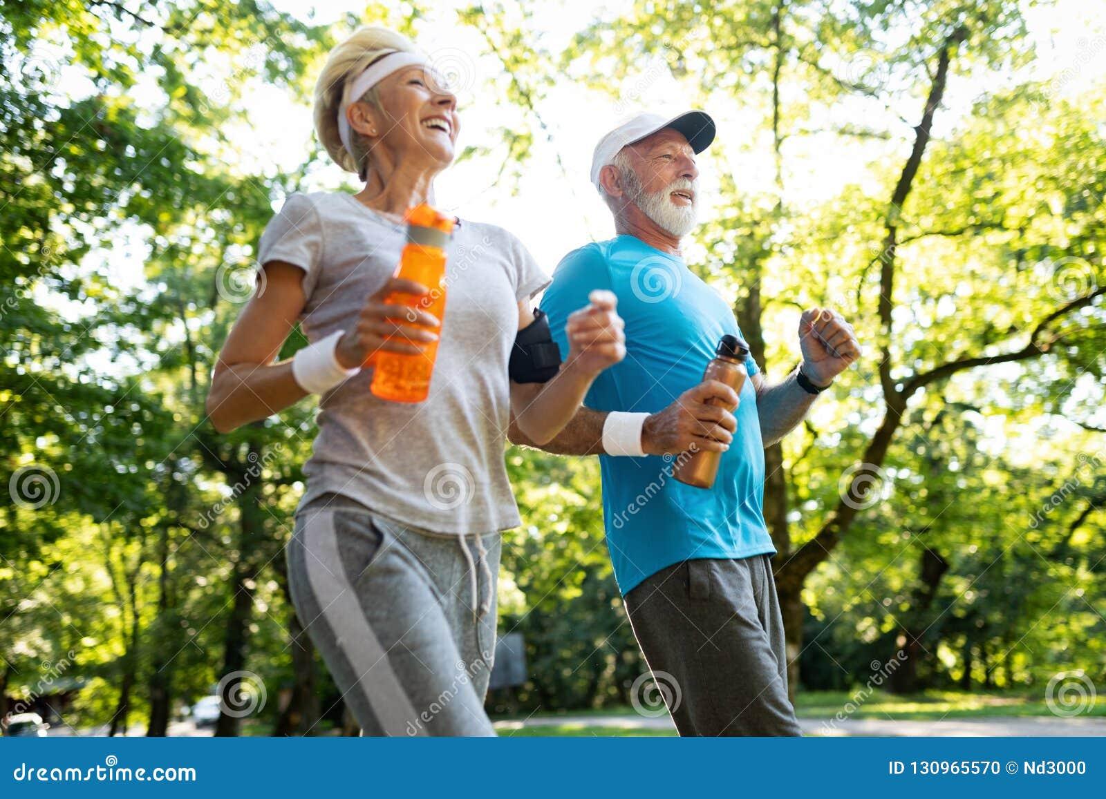 Fitness, sport, mensen, het uitoefenen en levensstijlconcept - het hogere paar lopen