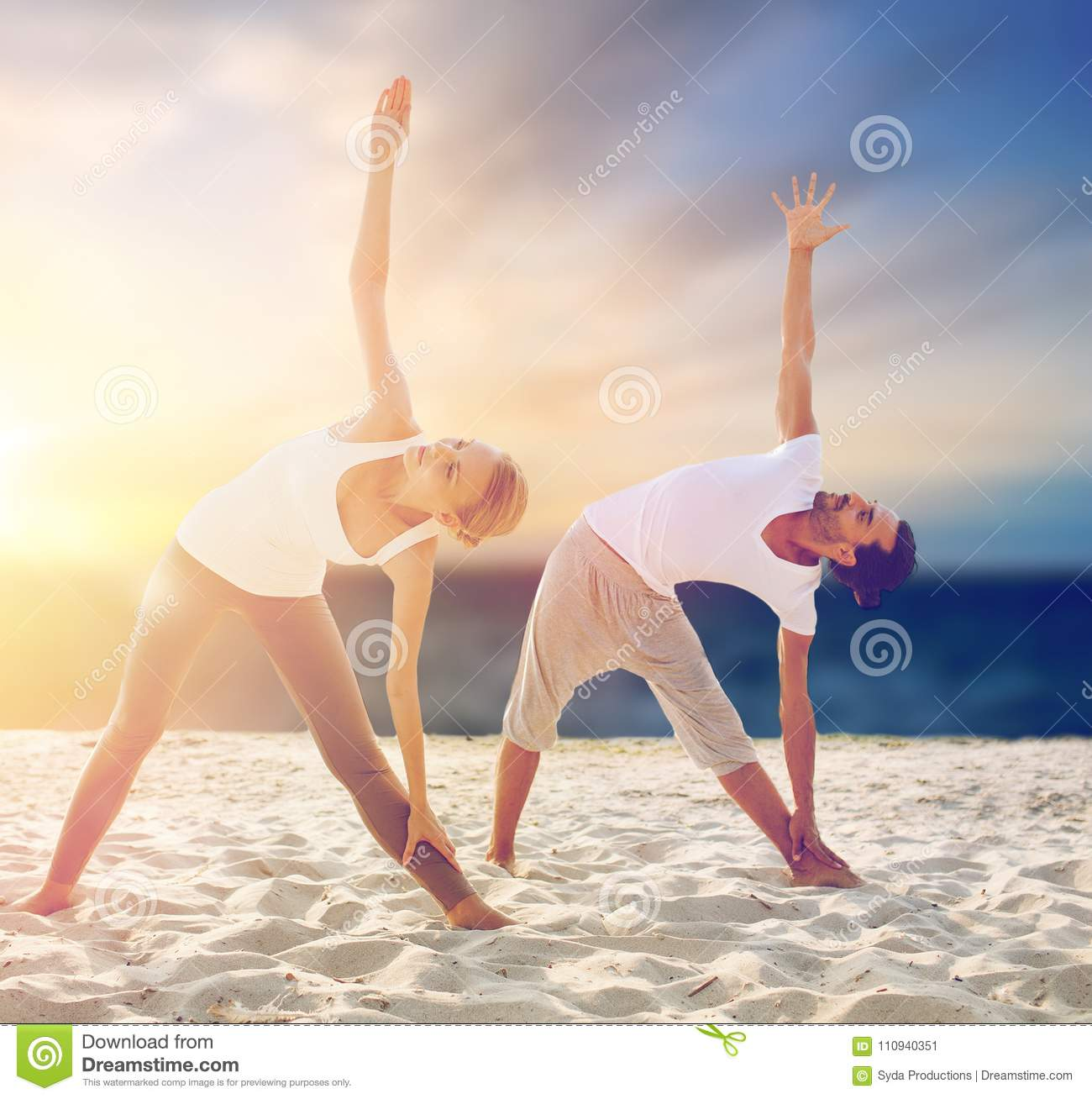 Couple making yoga exercises on beach