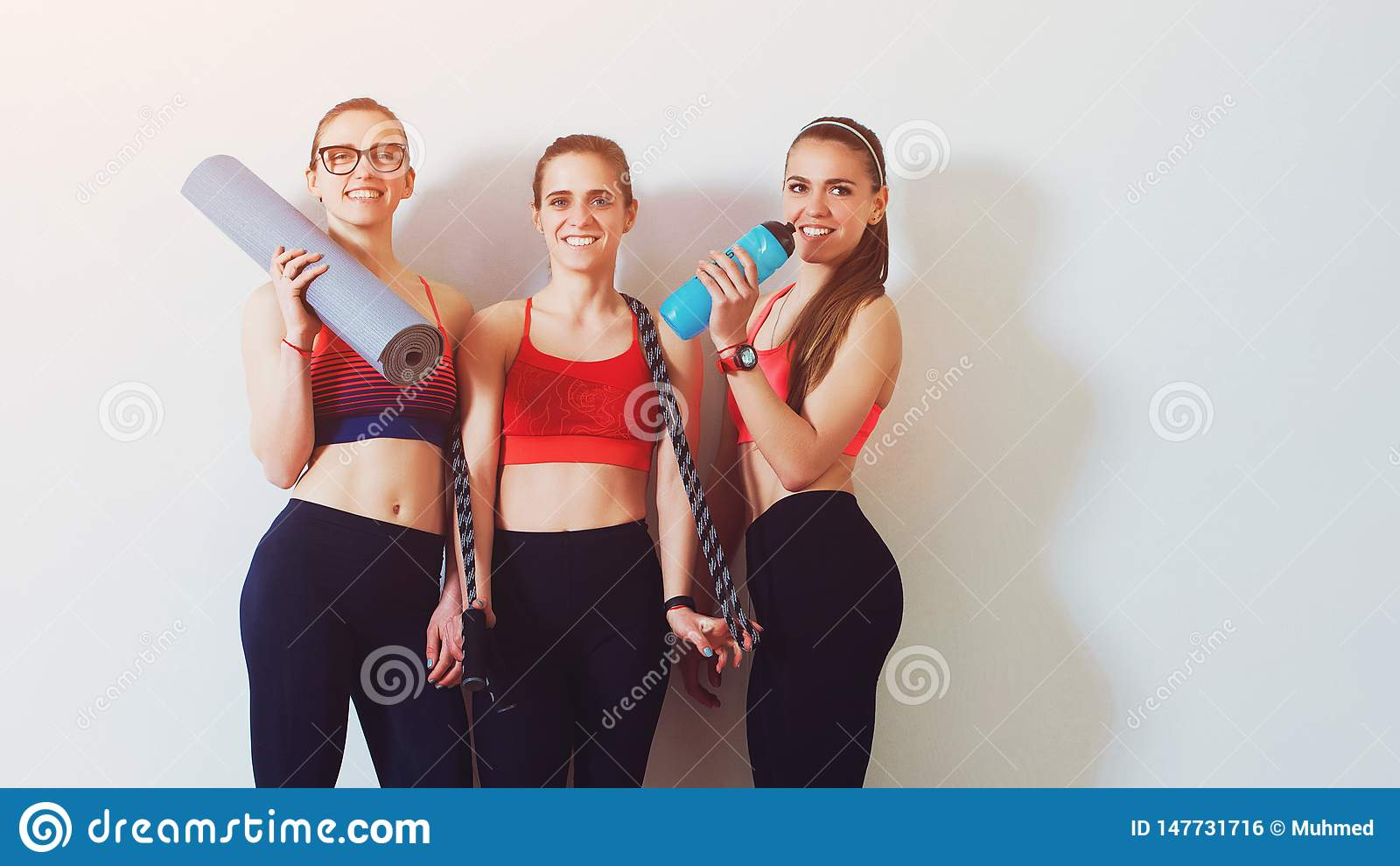 Fitness sportmeisjes Vrouwen die in sportenslijtage camera en het glimlachen bekijken Zij houden een fles van water en yogamat sp