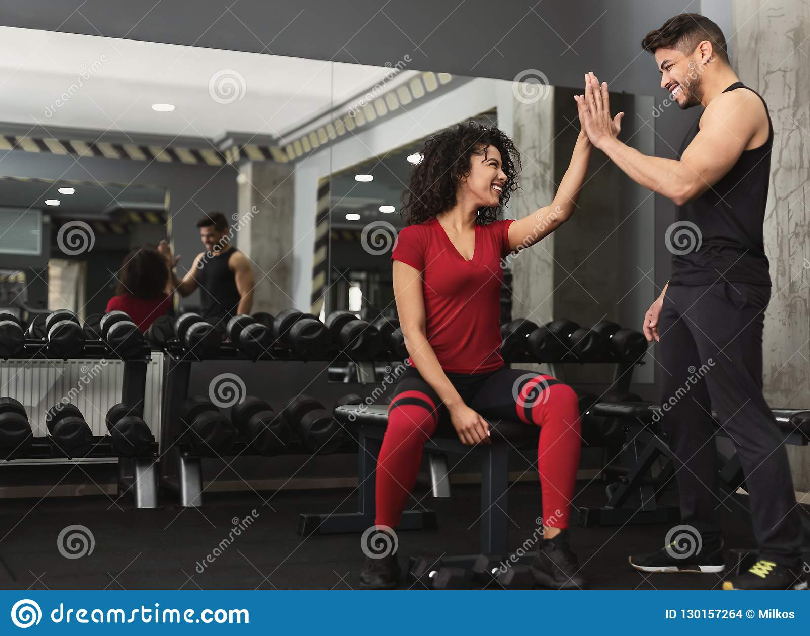 Fitness trainer and woman giving each other high five