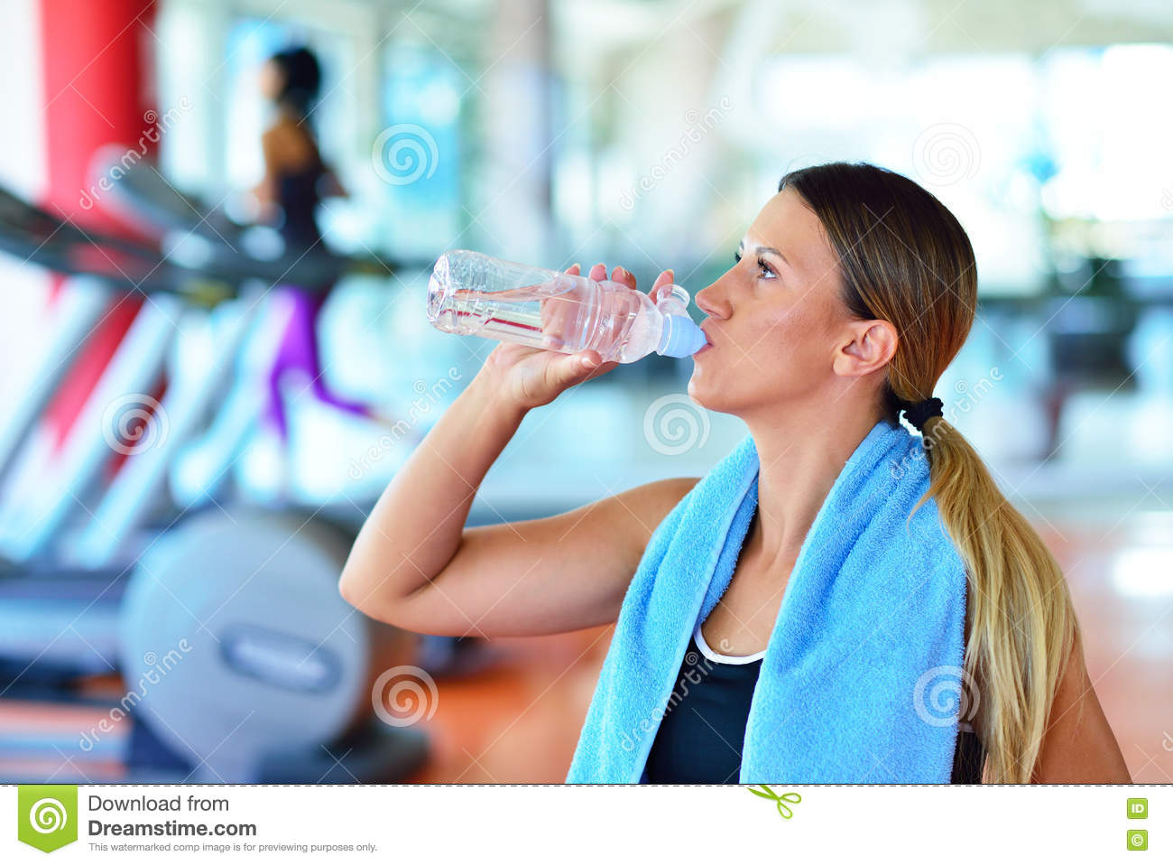 Fitness woman beautiful young girl in the gym drinking water beautiful young girl in the gym drinking water with blue towel sciox Gallery
