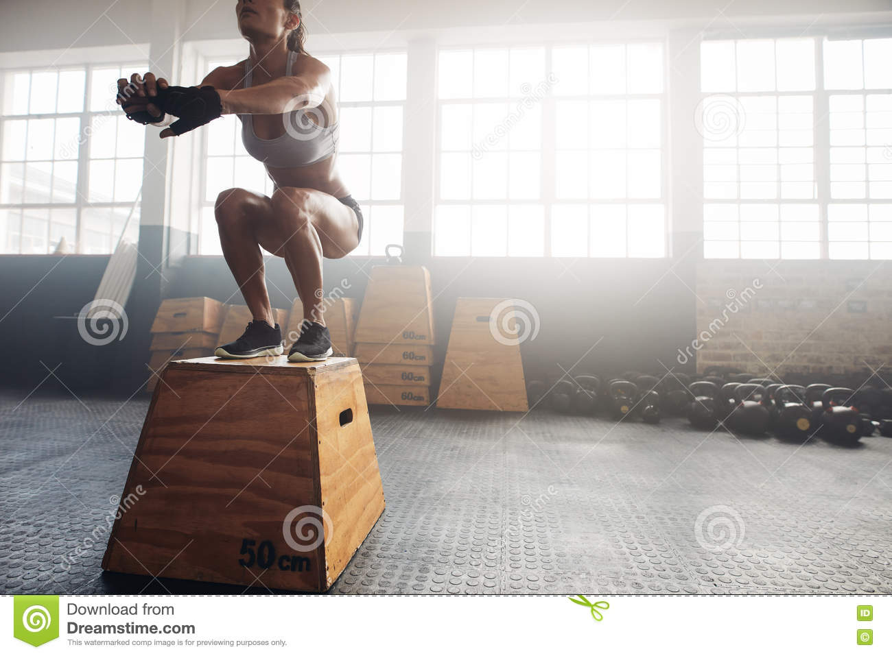 Fitness woman doing box jump workout at crossfit gym