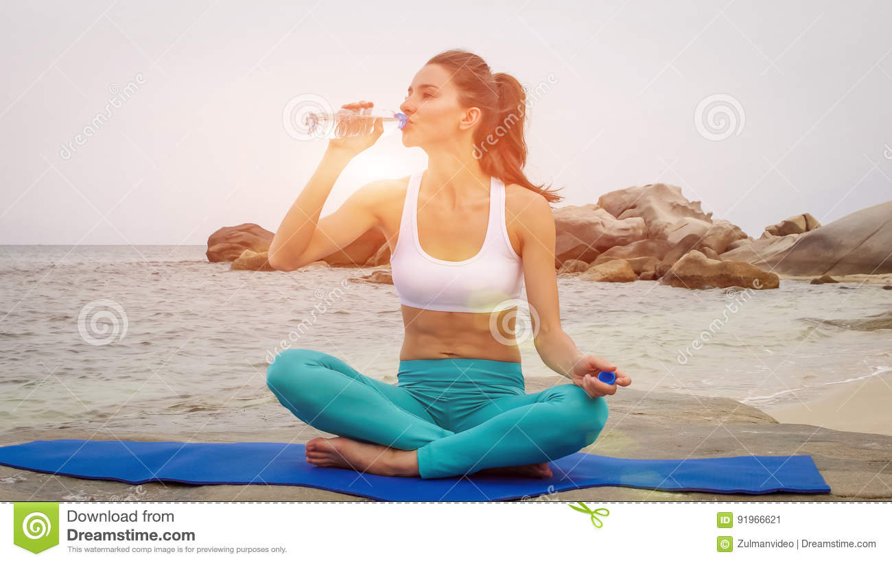 Fitness woman drink water after doing sport exercises on beach at sunset.