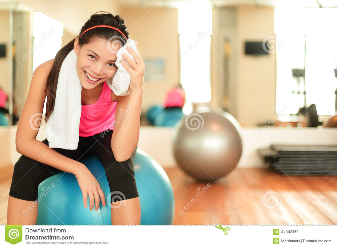 ec8298880ea Fitness woman in gym. Resting on pilates ball   exercise ball sweating  using towel relaxing