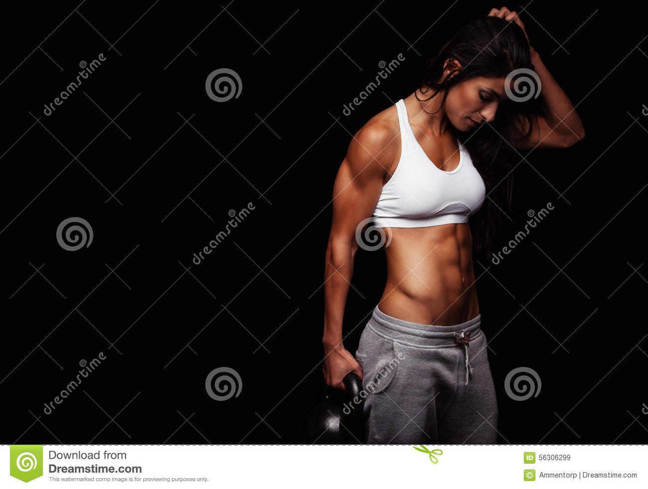 Fitness woman holding heavy kettle bell