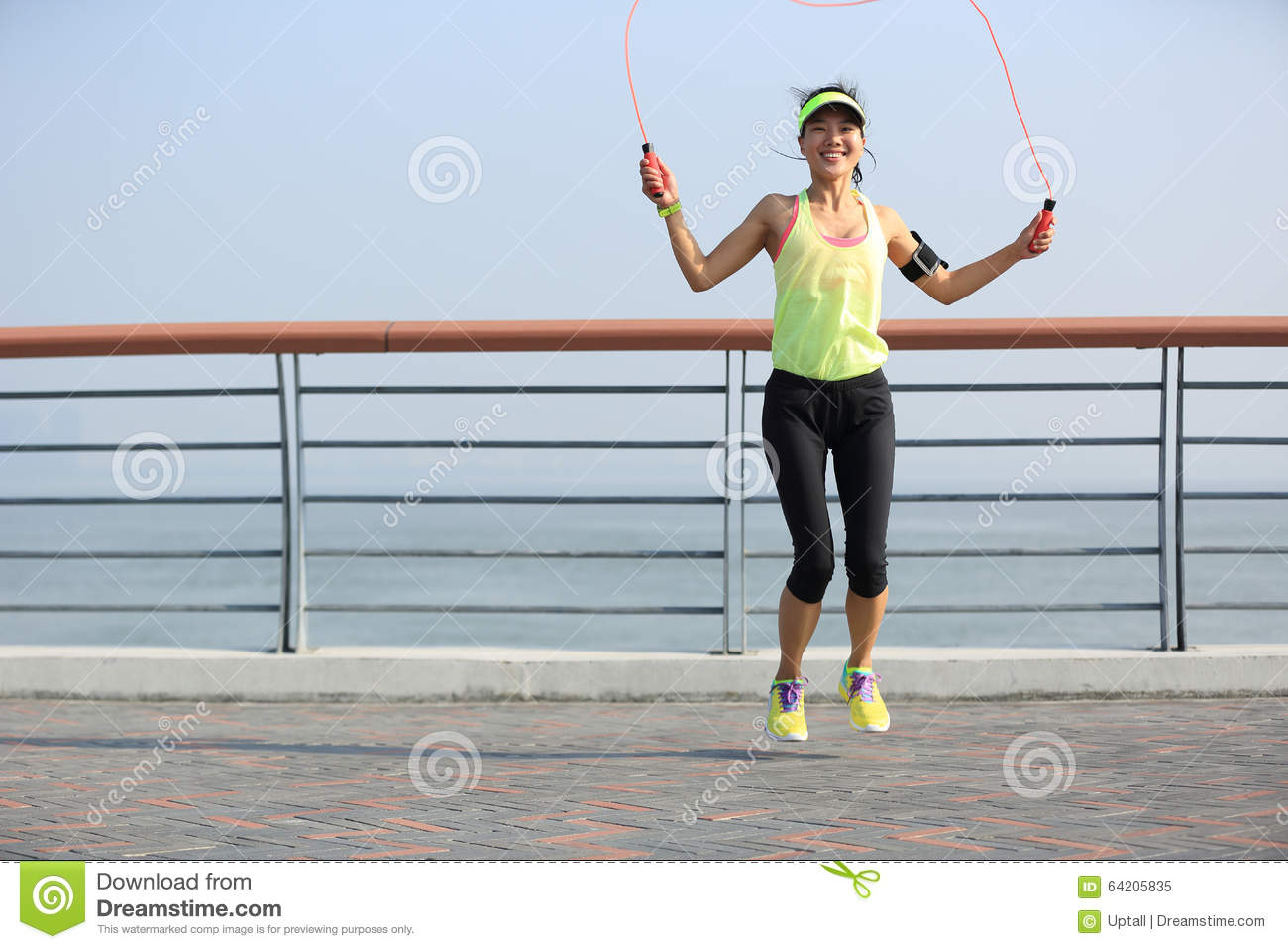 Fitness woman jumping rope at seaside