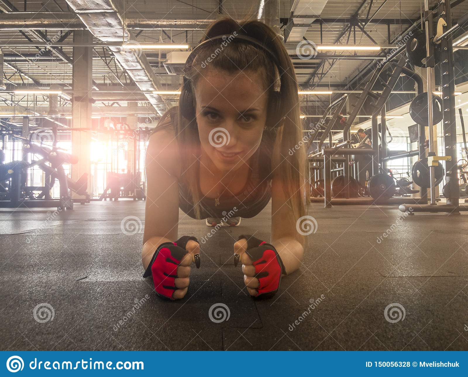 Fitness woman listening music in wireless headphones. Doing workout exercises in the gym. Beautiful athletic fit girl relaxing aft