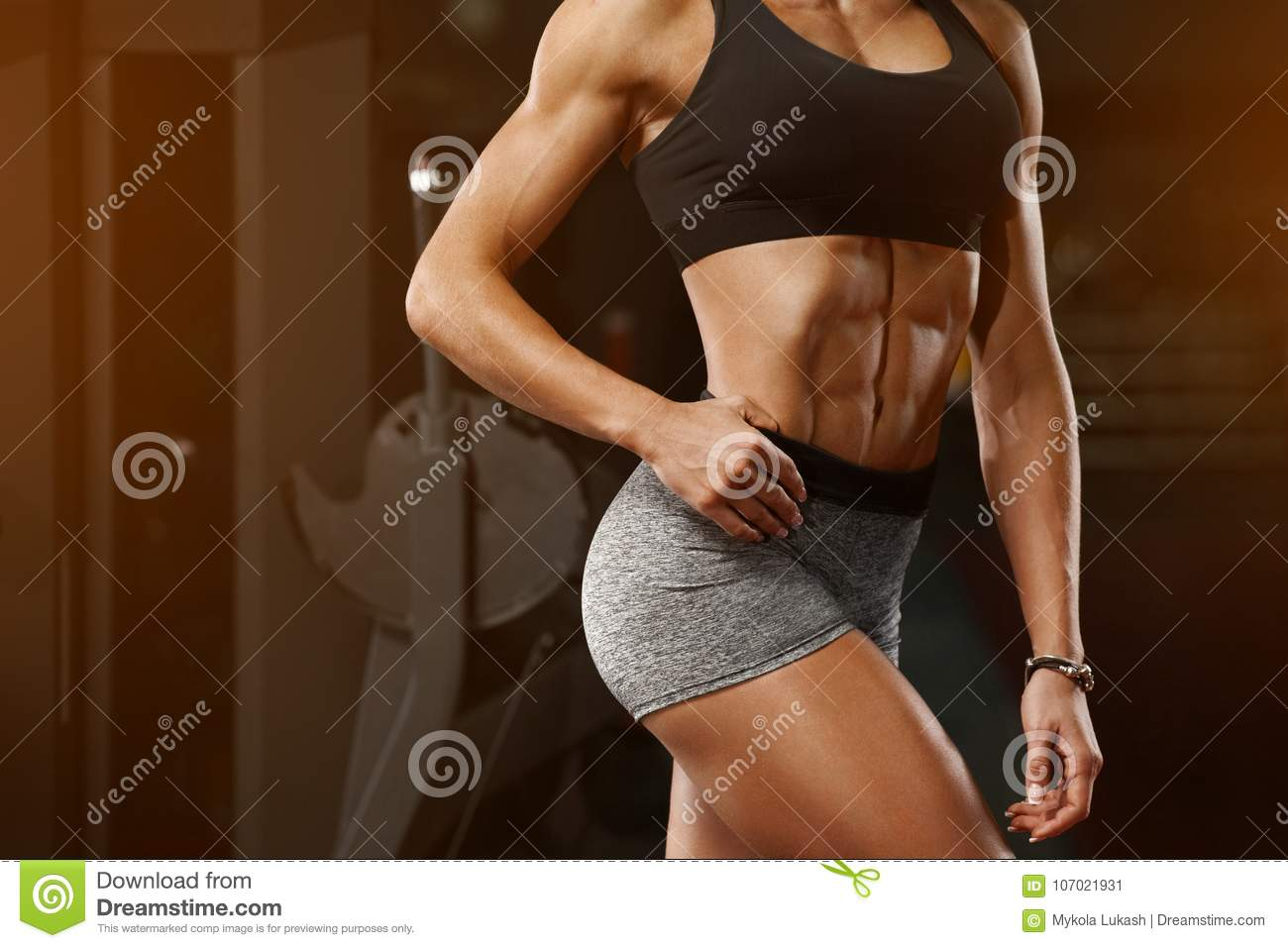Fitness woman showing abs and flat belly in gym. Athletic girl, shaped abdominal, slim waist