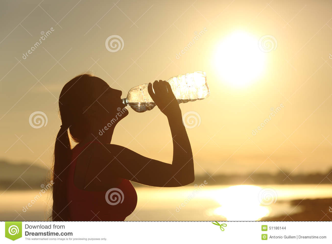 Fitness woman silhouette drinking water from a bottle