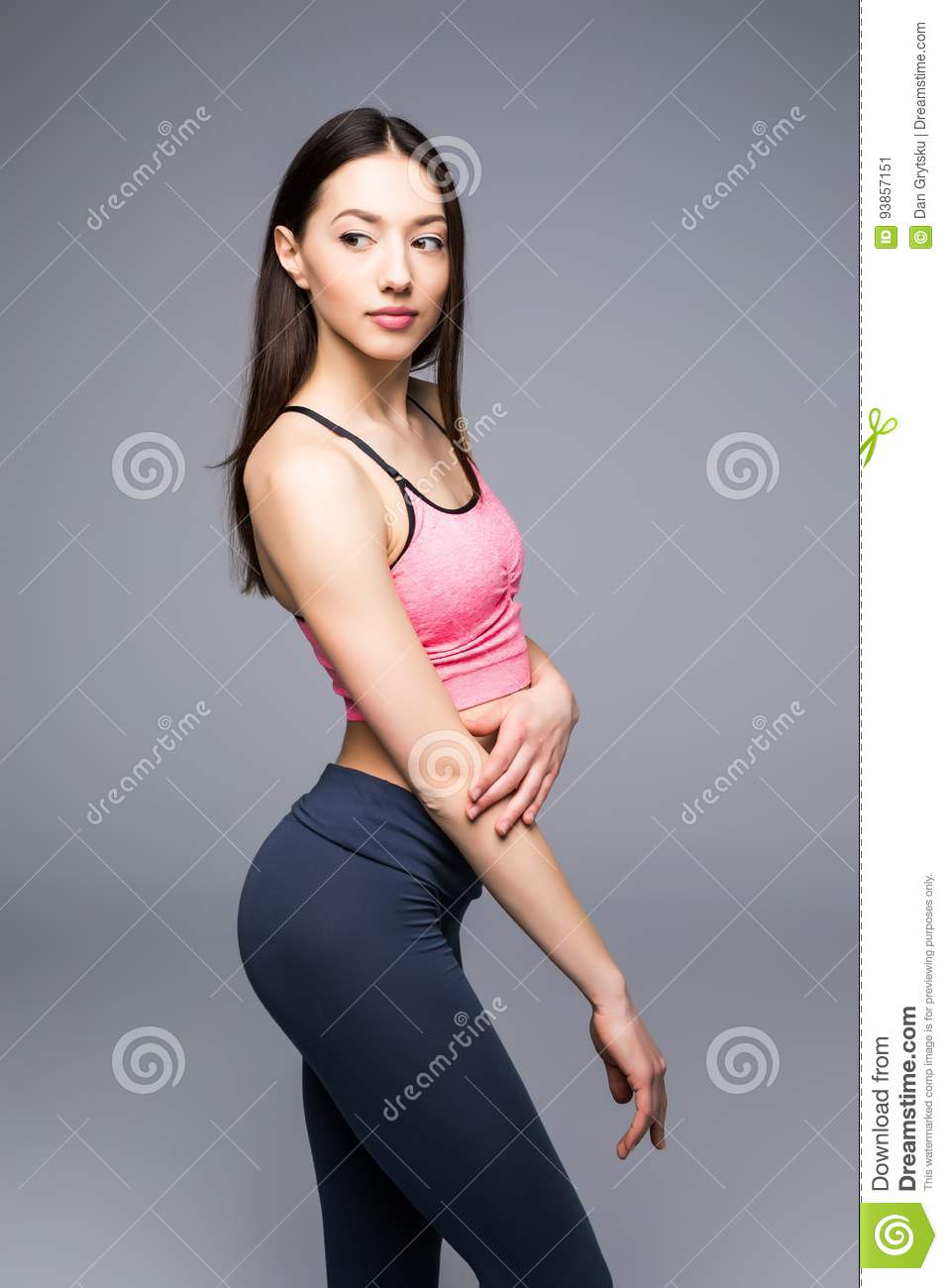 Fitness woman in sports clothes posing on gray background, studio shot