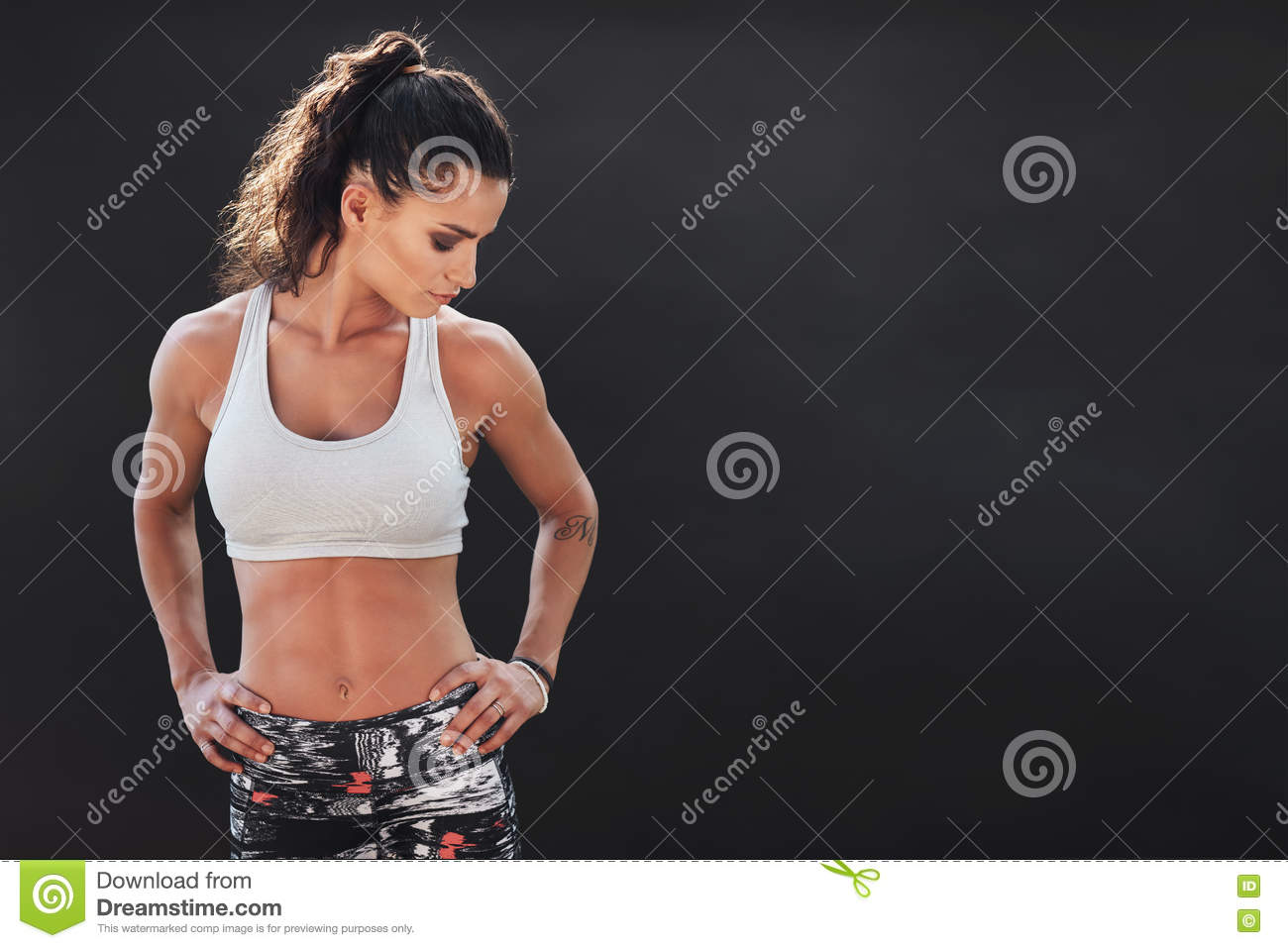 c602f38e Shot of young fitness woman standing with her hands on hips and looking  down on black background. Fit young female model with copy space.