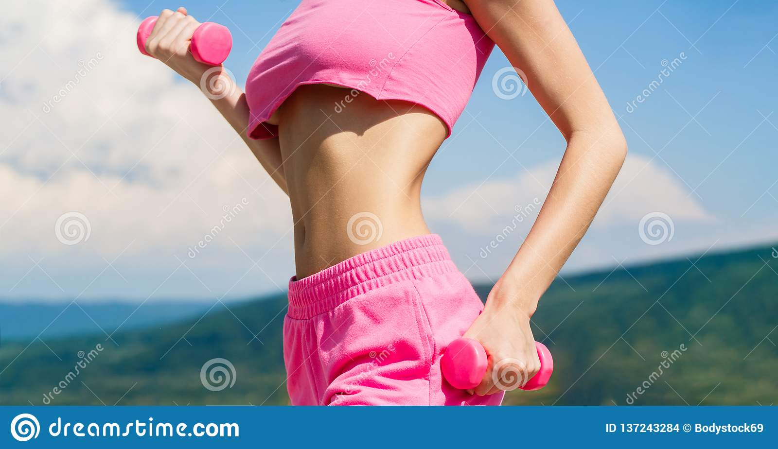 Fitness woman in training. Sporty woman does the exercises with dumbbells. Sports fitness girl, dumbbells. Woman