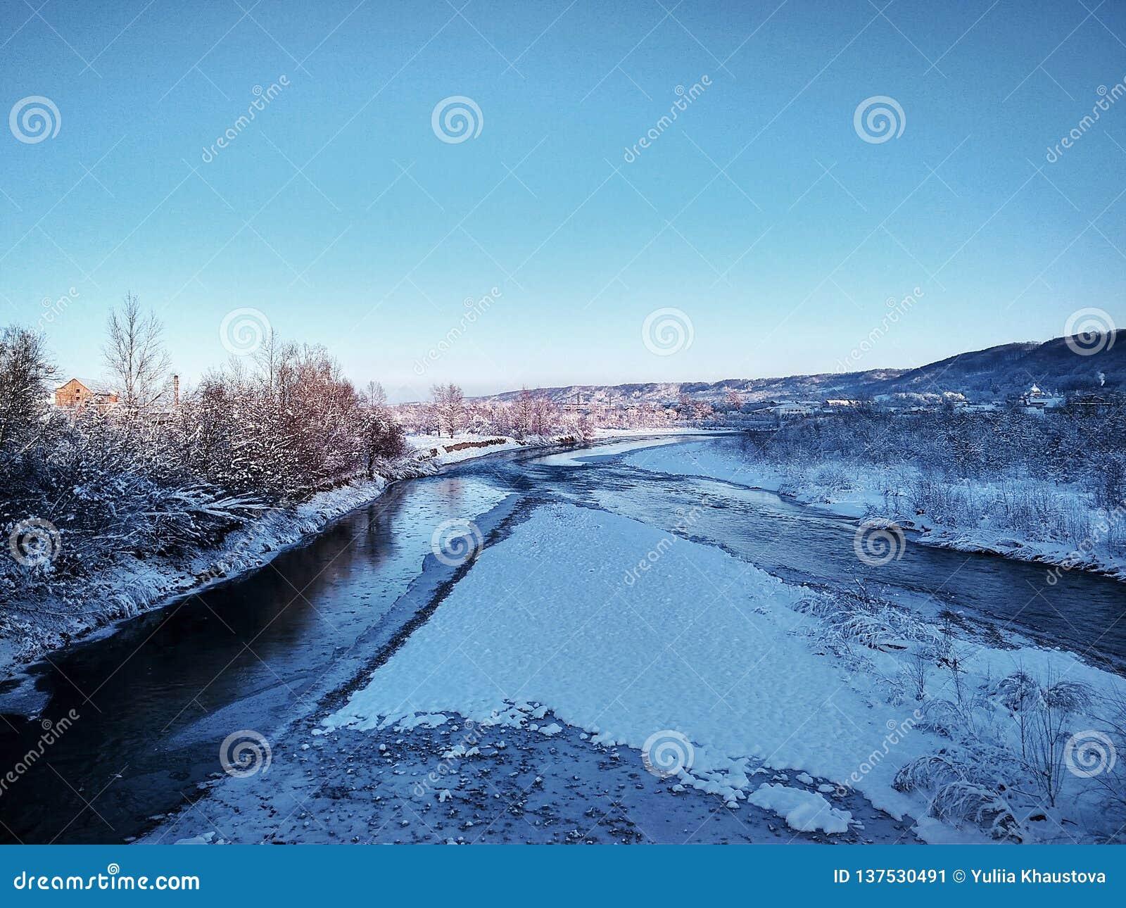 Fiume con ghiaccio su un fondo delle montagne