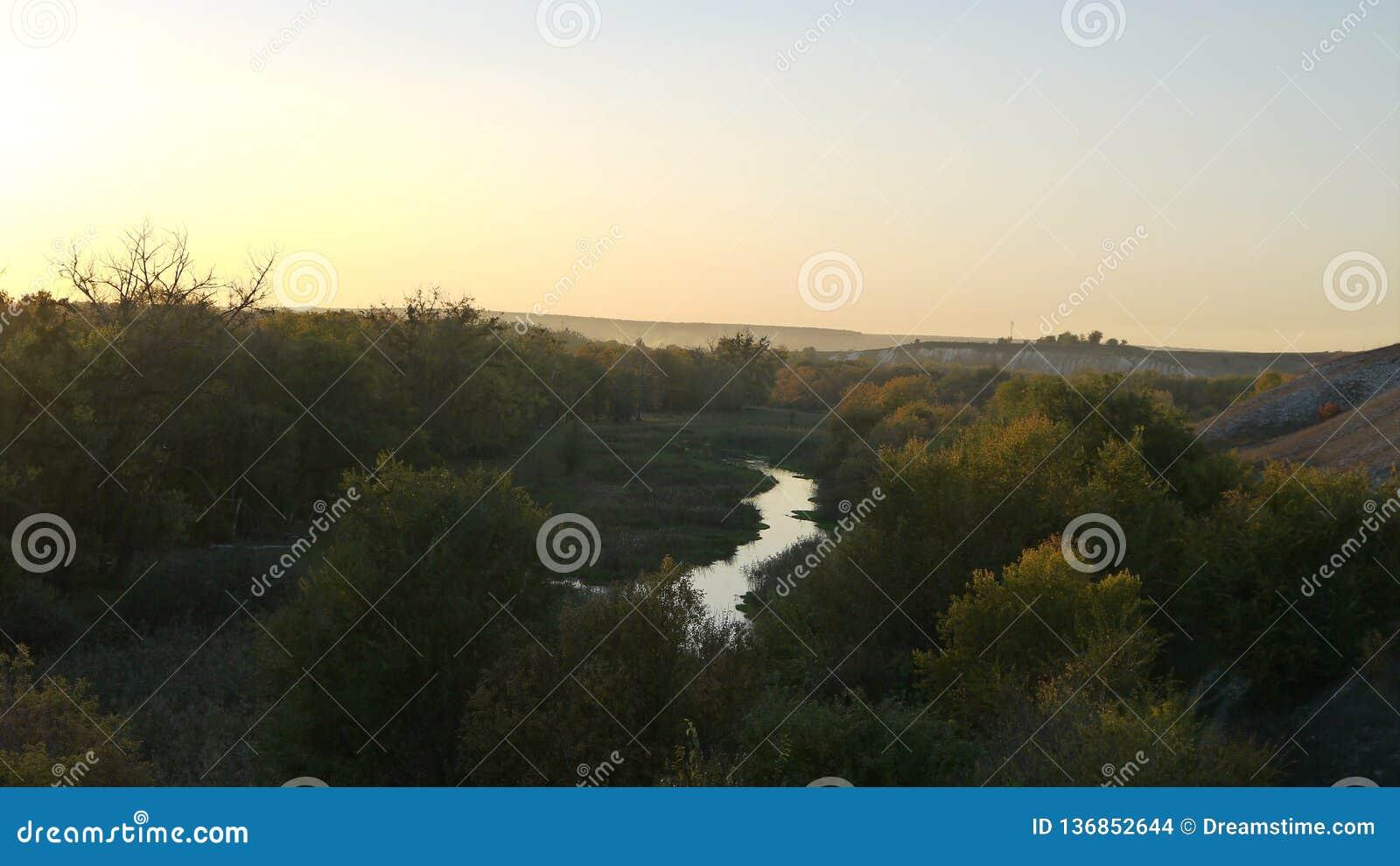 Fiume nella valle contro il contesto del sole di autunno di tramonto
