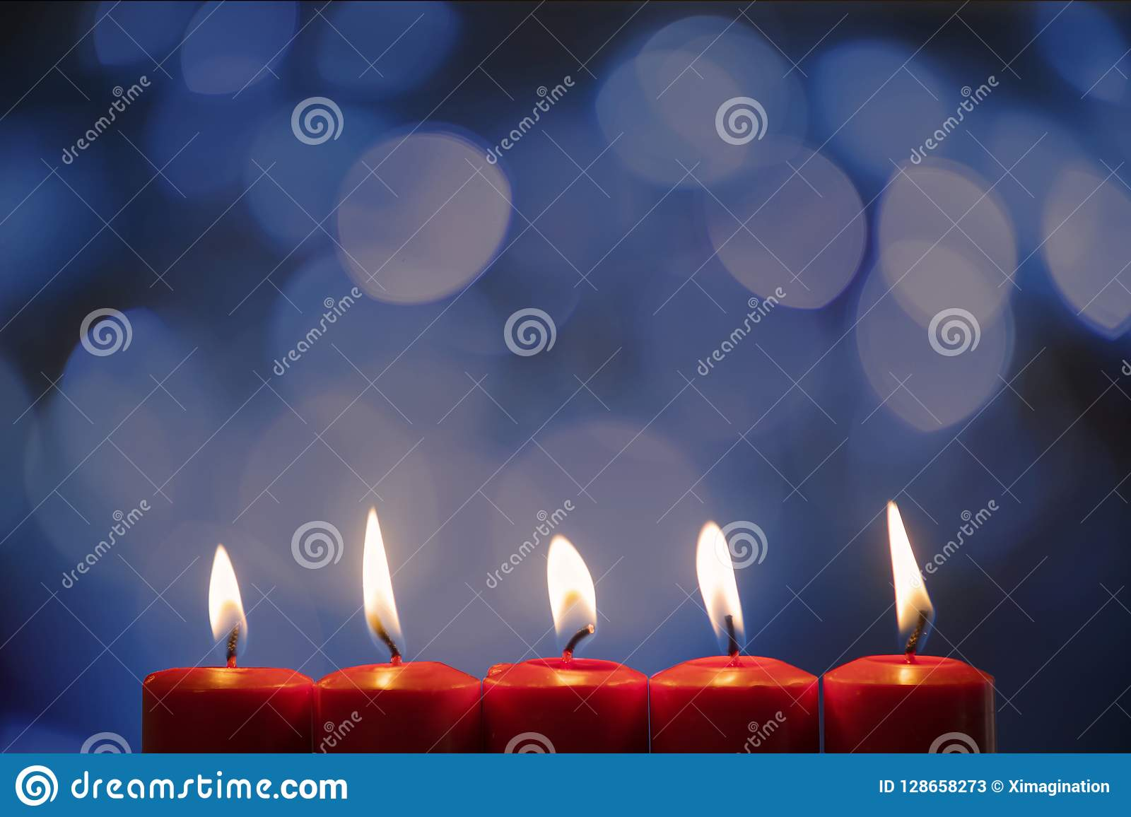 Closeup Of Five Burning Candles With Blurred Sparkling Light Background