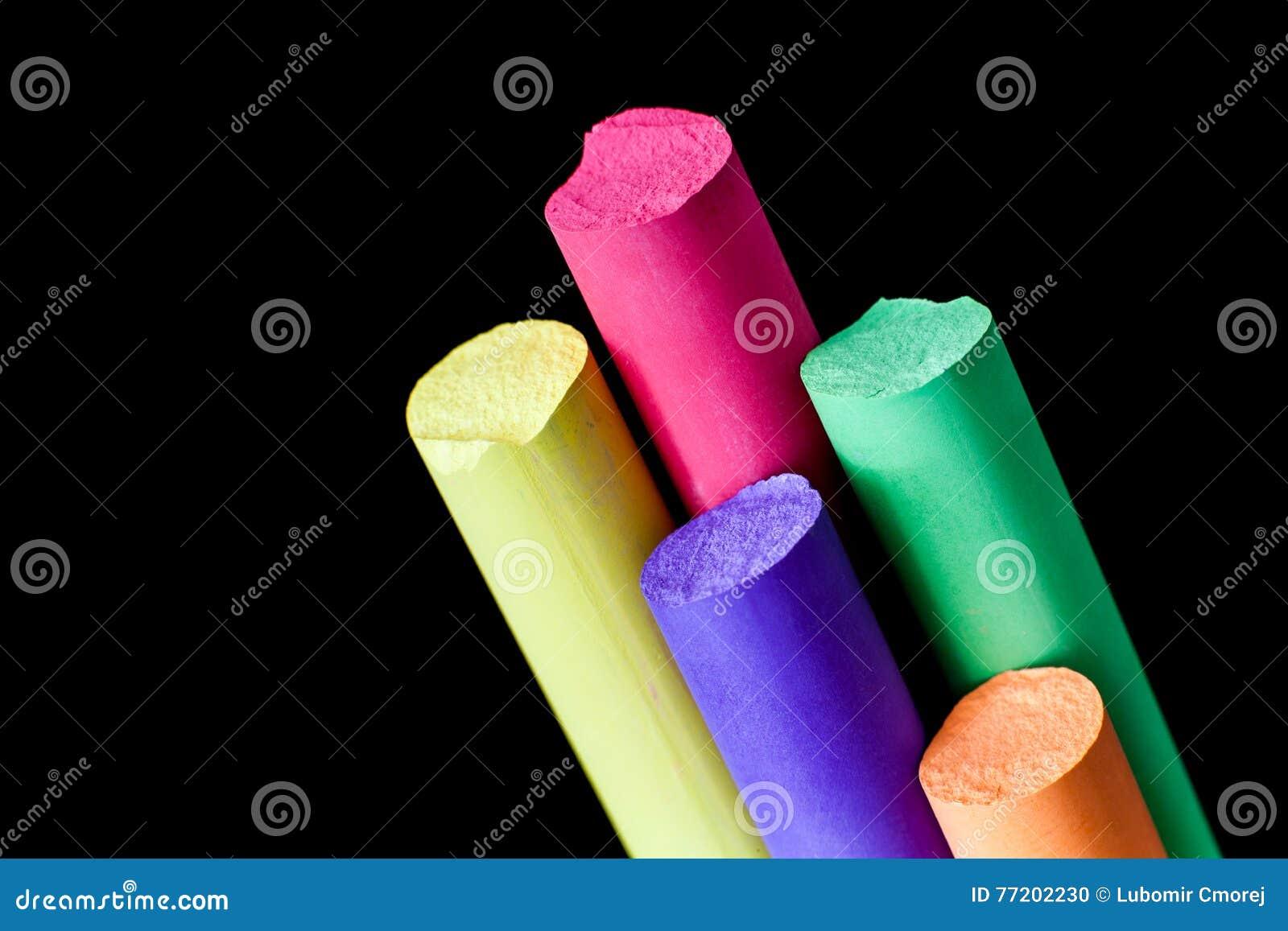 Five colore chalks on a black