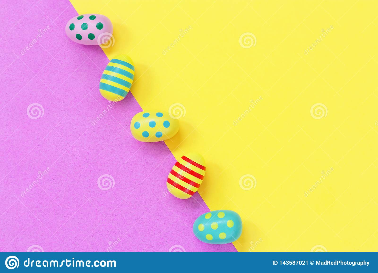 Five colourful Easter eggs against a yellow and pink diagonal background