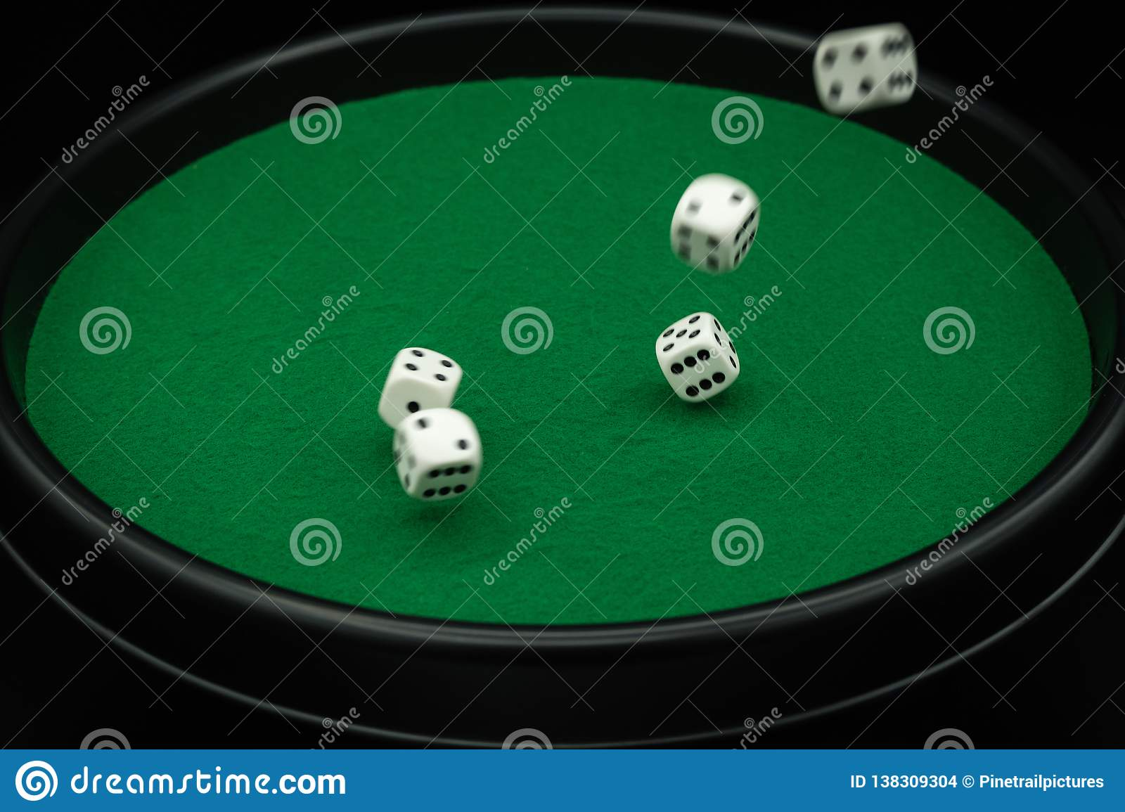 Five dice in motion on green dice board