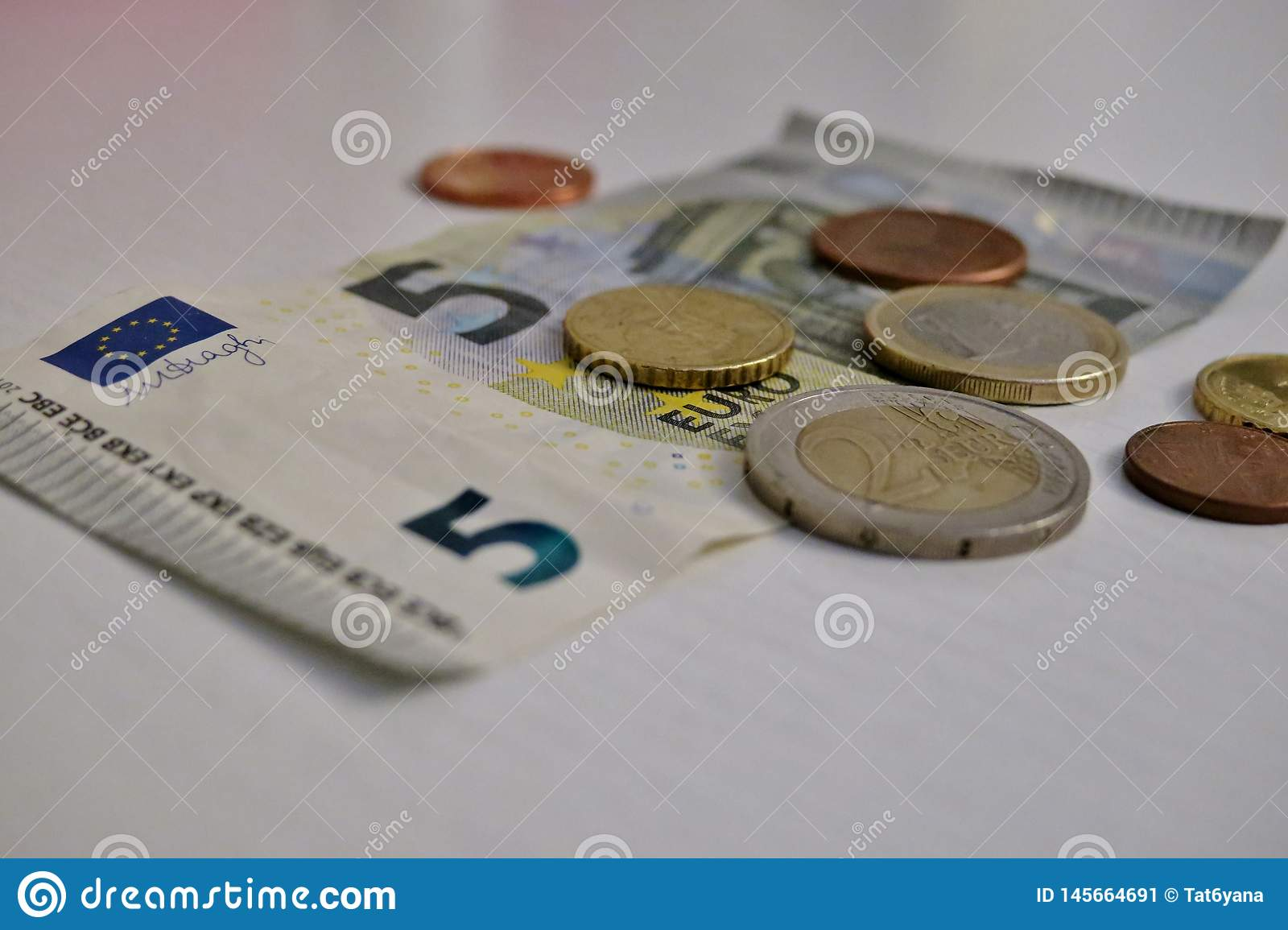 Five euro and a penny on a white background close-up