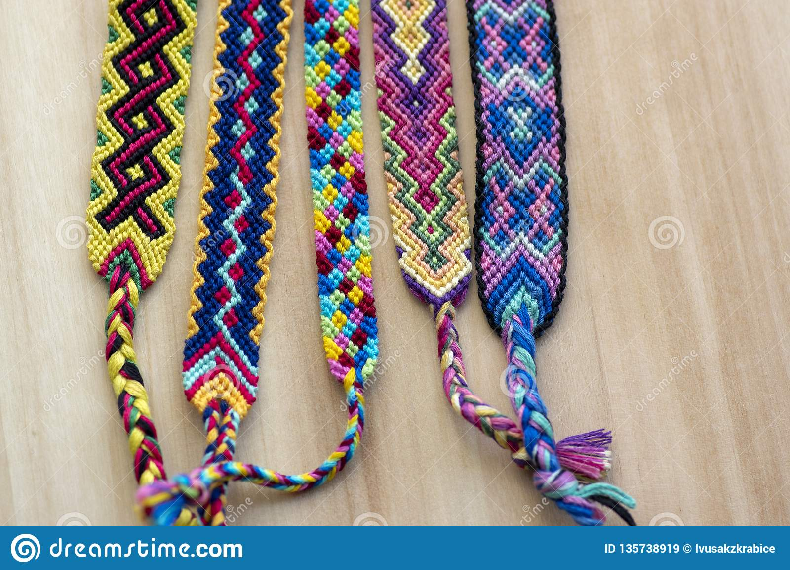 5299a7014c1 Five handmade homemade colorful natural woven bracelets of friendship on  wooden board