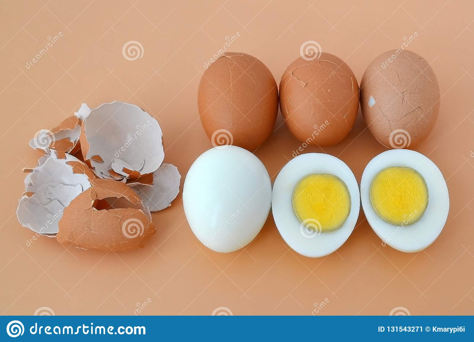 Five hard boiled brown chicken eggs on a brown background