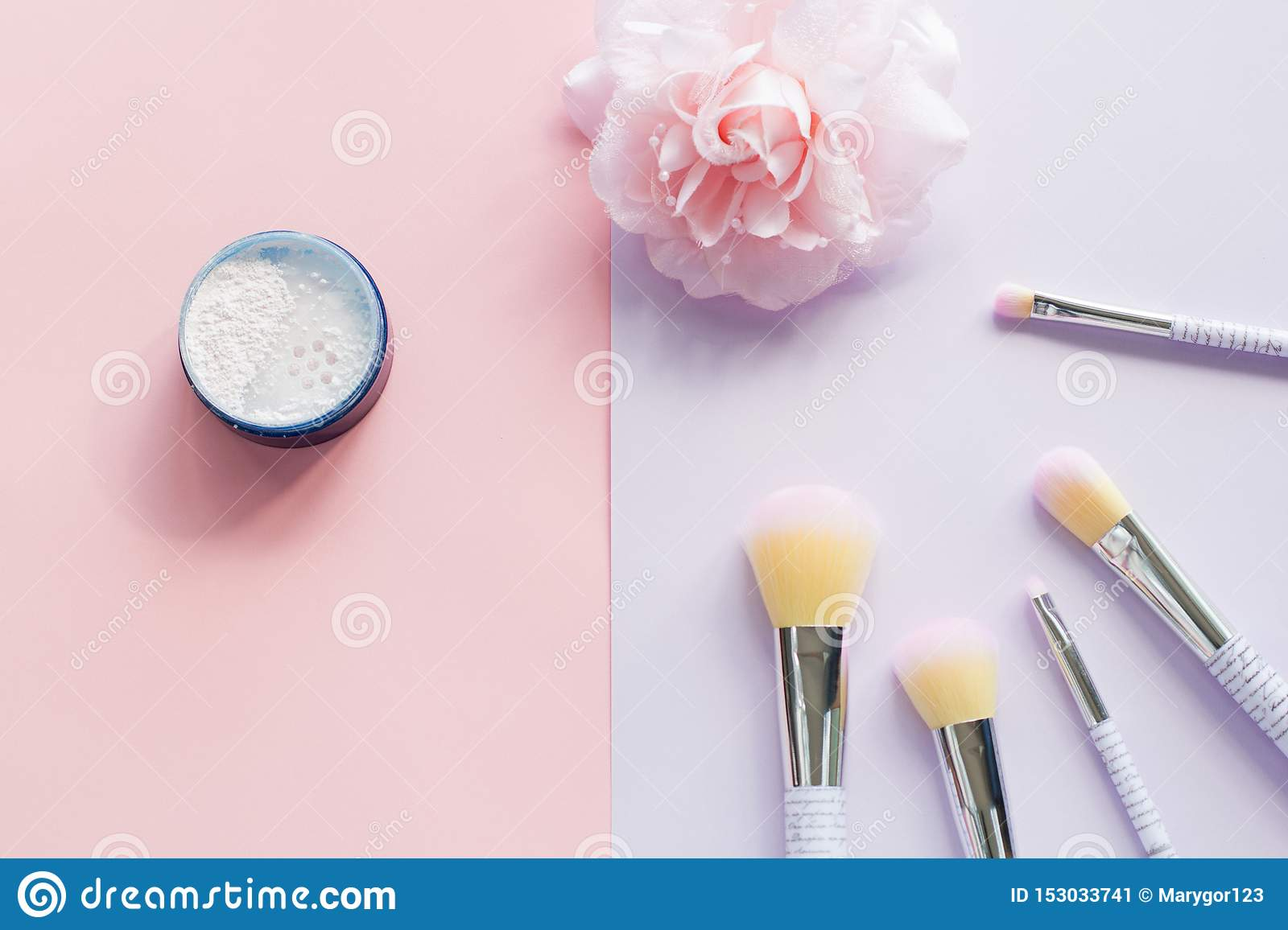 Five makeup brushes with lettering on the handle and mineral powder in a blue jar, bobby pin