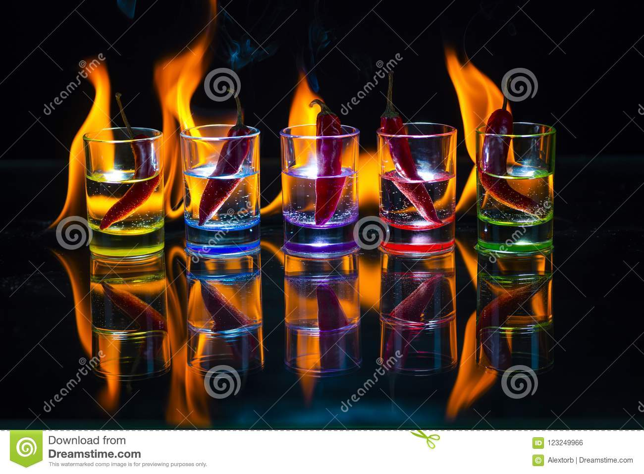Five multicolored shot glasses full of drink and with the red ch