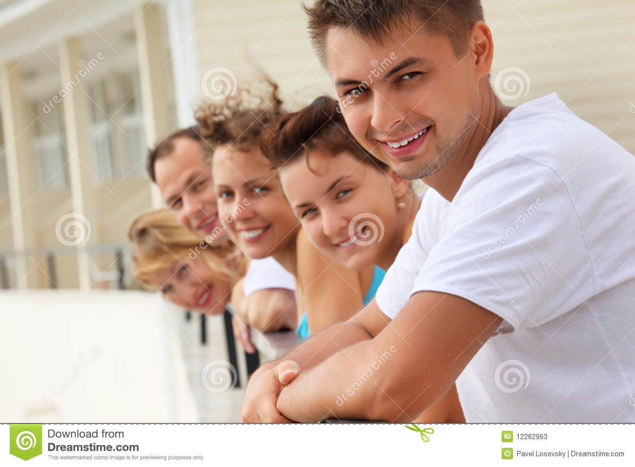Five smiling friends on balcony