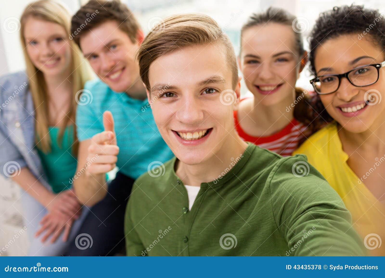 Five smiling students taking selfie at school