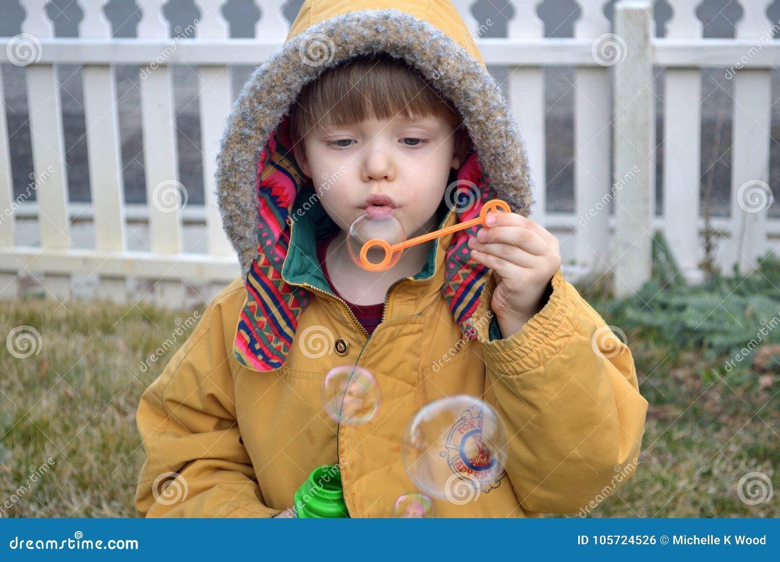 Boy blowing bubbles in the yard in winter
