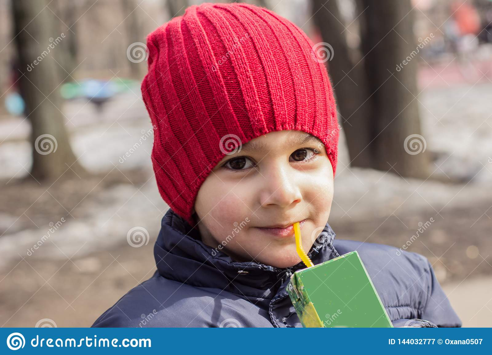 The child drinks juice in the Playground. emotional close-up portrait.