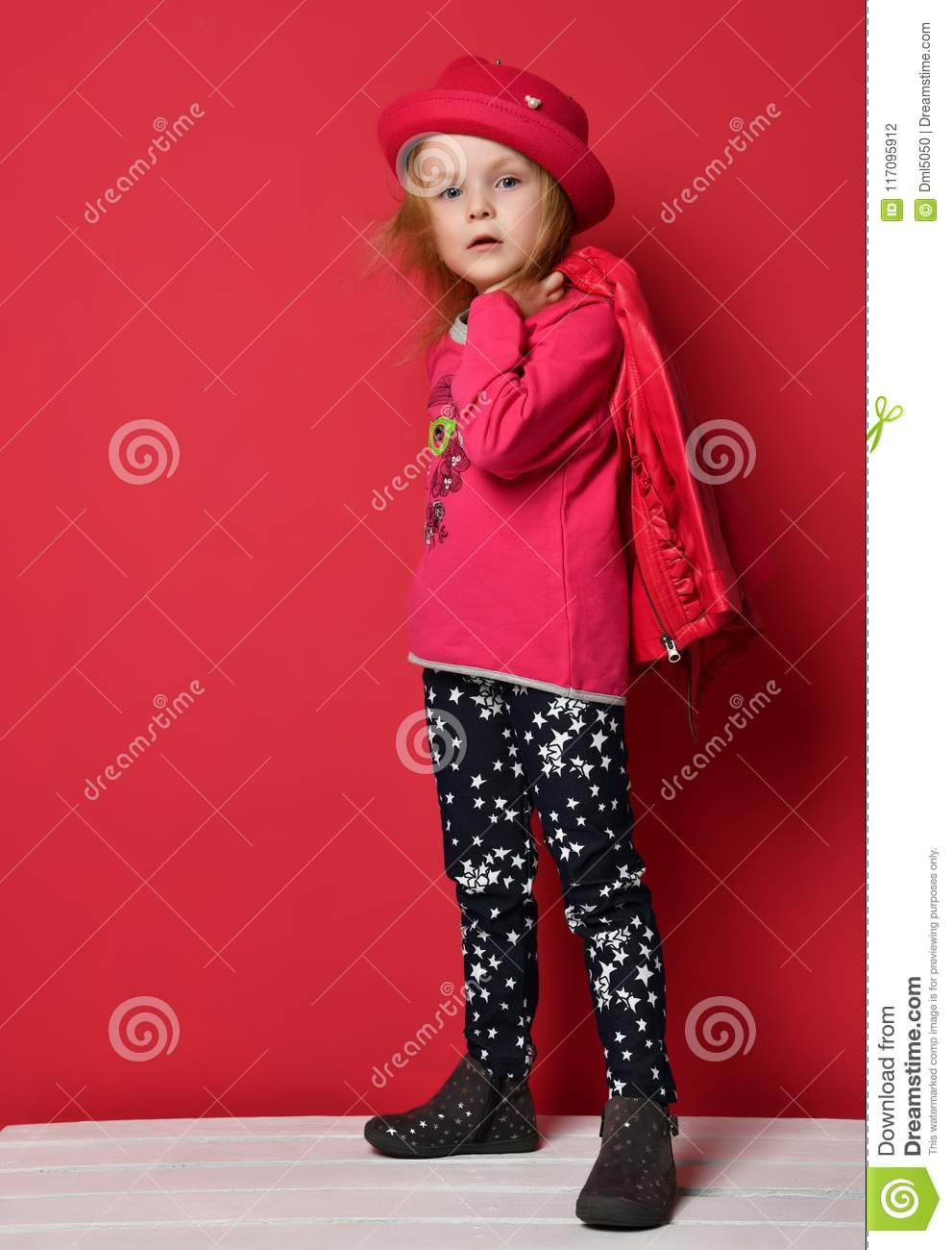 Five years old baby girl child kid posing in red leather jacket and hat on red