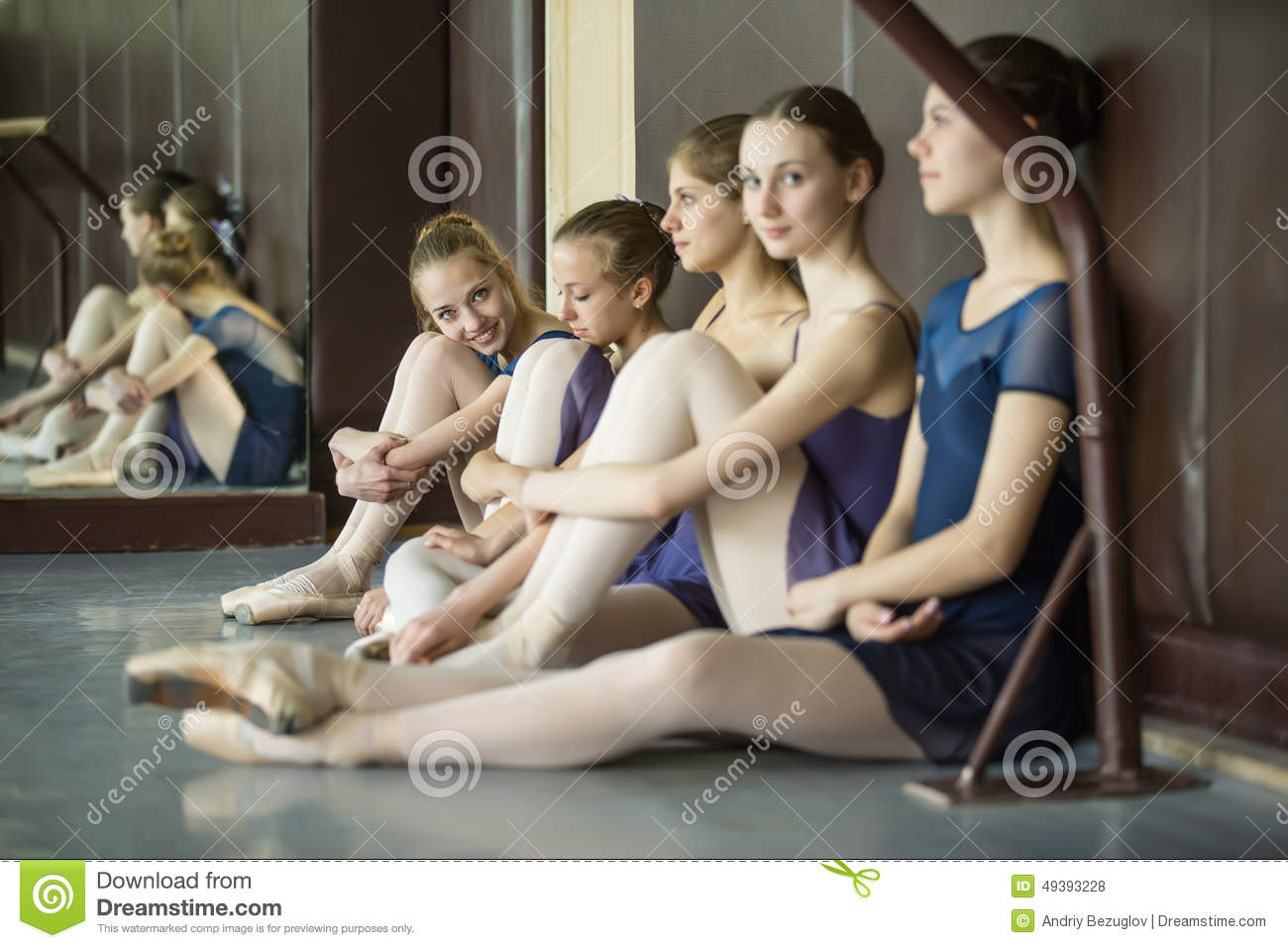 Five young dancers in the same dance costumes resting for Dance where you sit on the floor