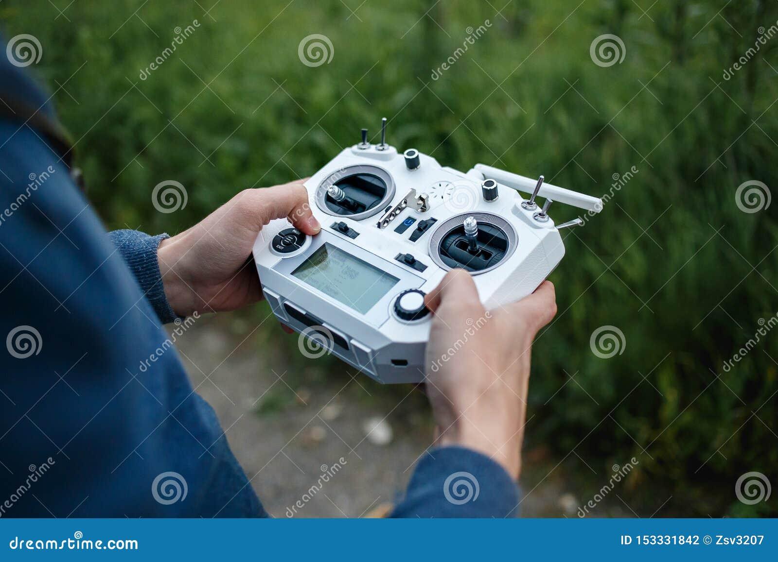 Fj?rrkontroll f?r quadrocopter, n?rbild S?ndare f?r att kontrollera den r?rande apparaten i manliga h?nder, suddig natur