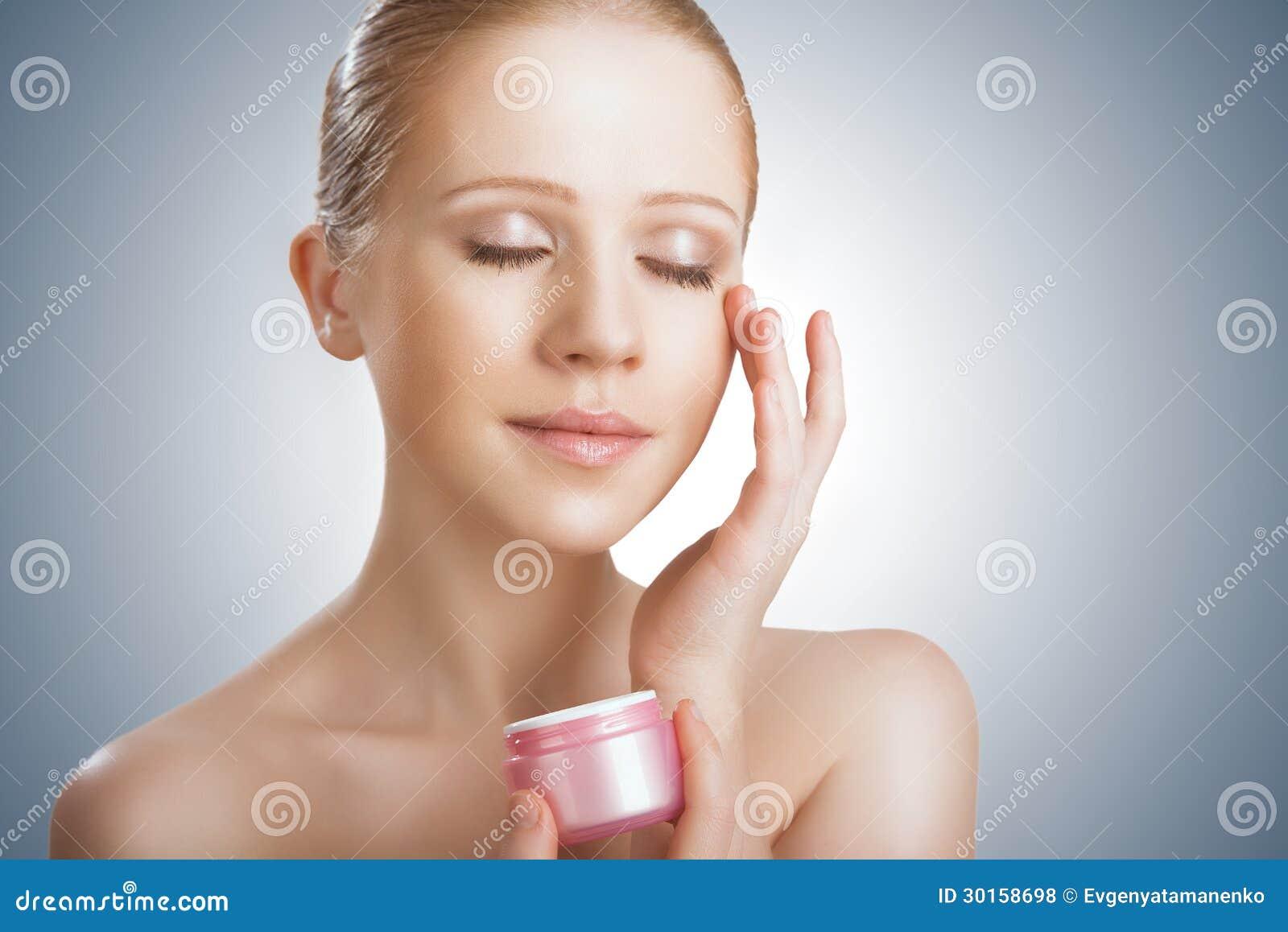 Flå omsorg. skönhetflickan med synar stängt med kruset av kräm