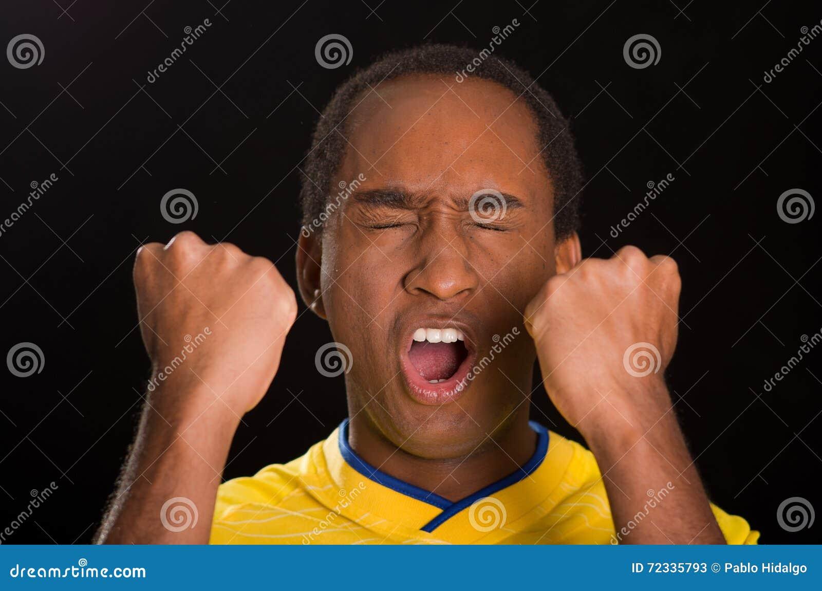Flådde manliga bärande gula fotbollskjortan för headshoten synar den mörker framme av svart bakgrund, den öppna stängt och munnen