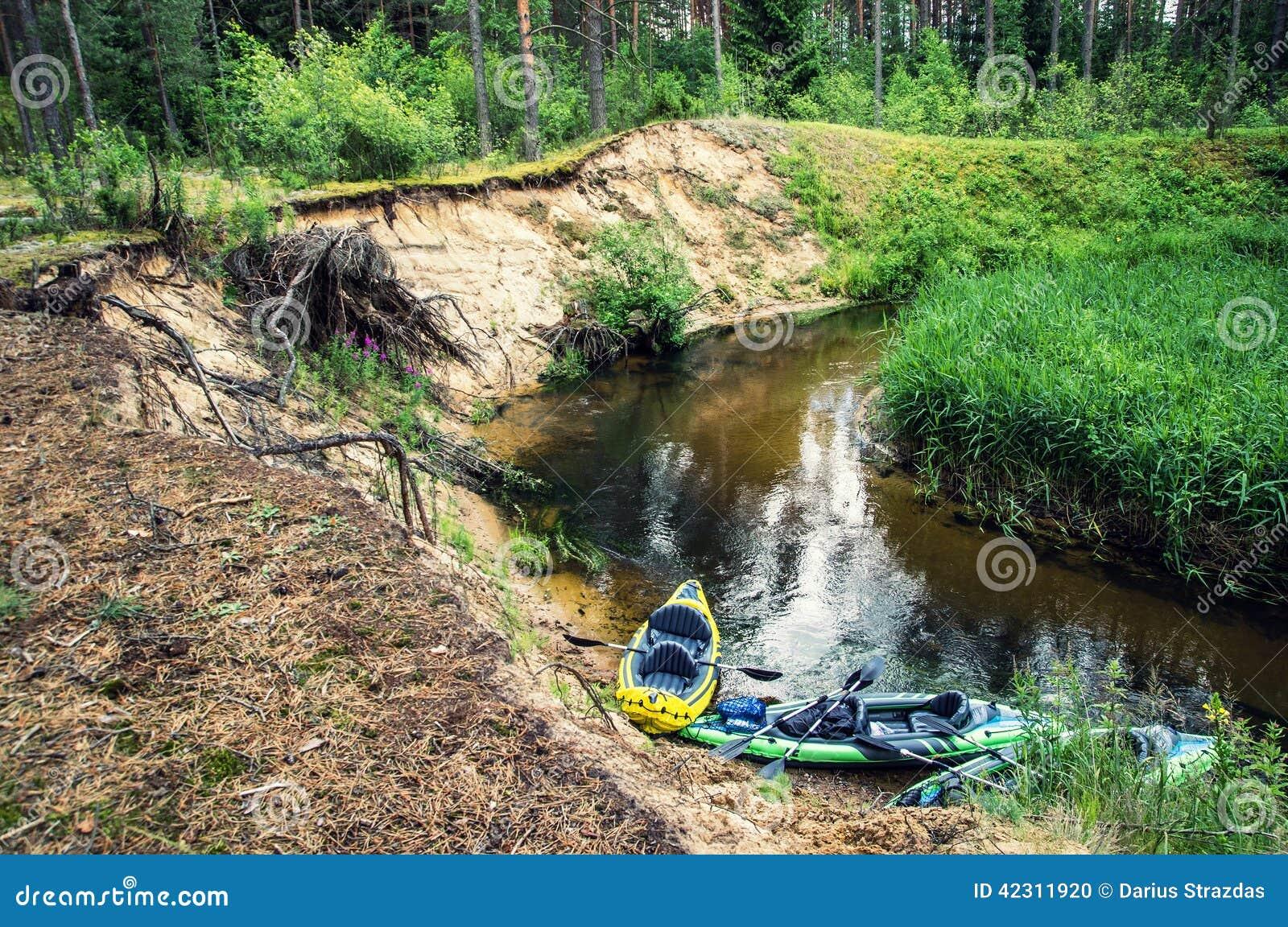 Flödande flod och kanoter på kusten