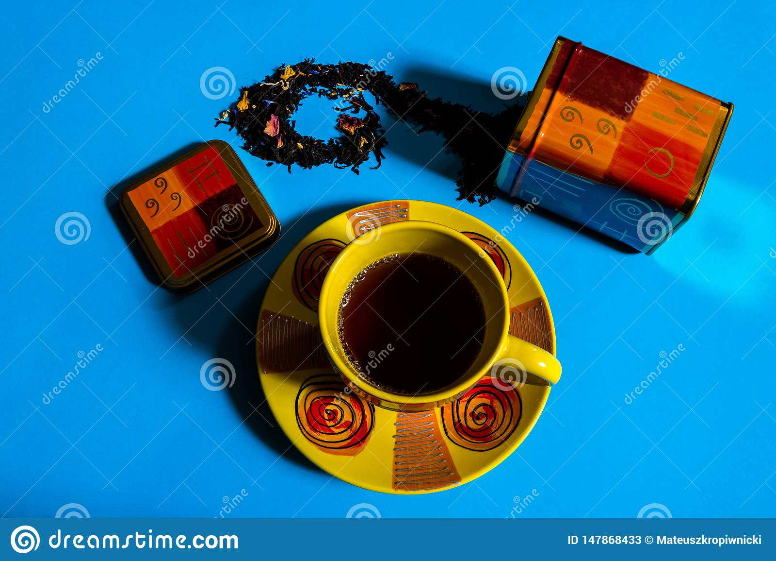 Flache Ansicht des Teezeitkonzeptes mit bunter Teeschale, Teebeh?lter, loser schwarzer Tee auf blauem Hintergrund