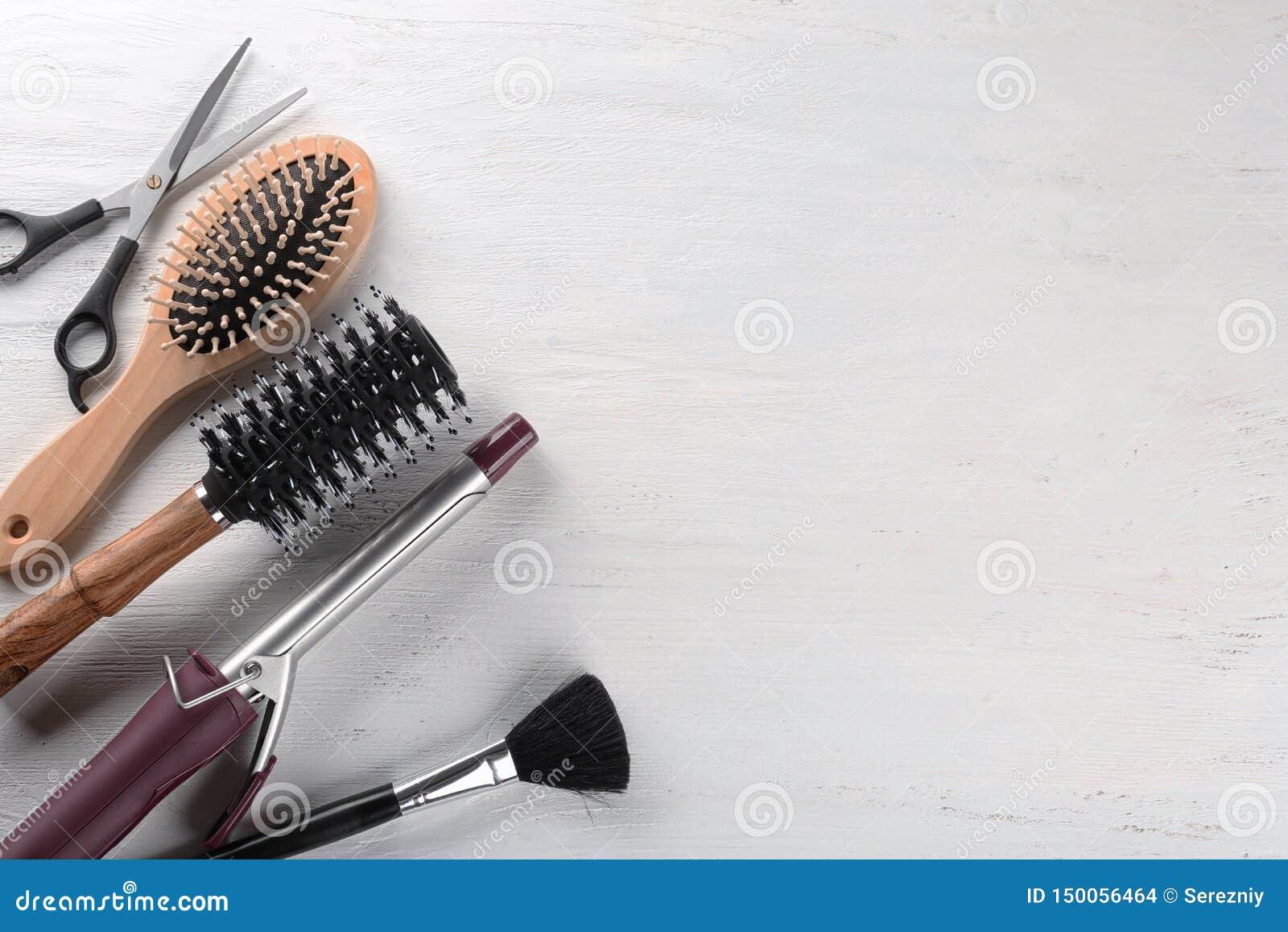 Flache gelegte Zusammensetzung mit Satz Friseur  's-Werkzeugen auf hellem Hintergrund