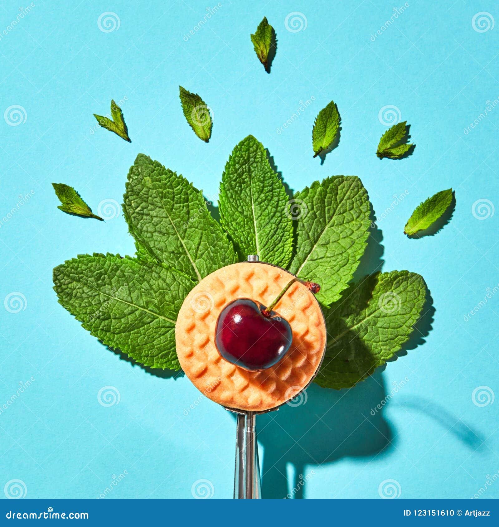 Flache Lage des Löffels für Eiscreme mit tadellosen Blättern, Keks und Kirsche auf einem blauen Hintergrund mit harten Schatten N