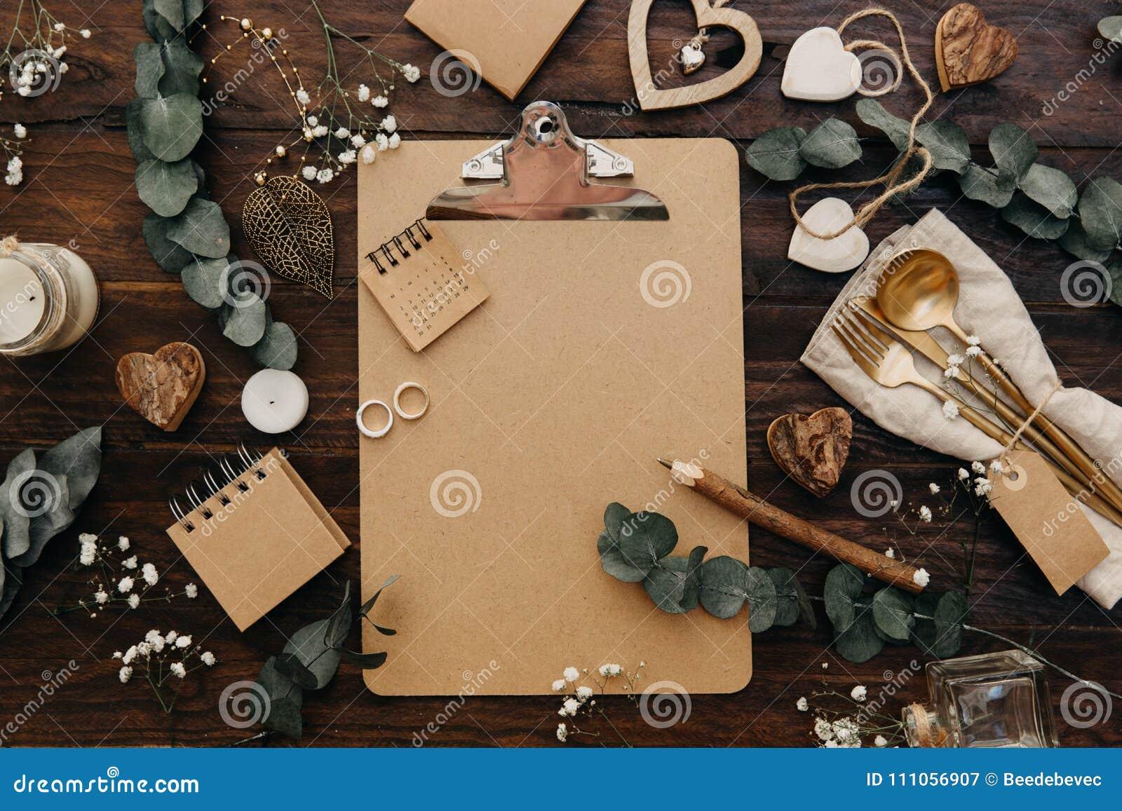 Flache Lage Hochzeitsplanung Machen Sie Klemmbrett mit rustikalen Dekorationen auf hölzernem Hintergrund in Handarbeit