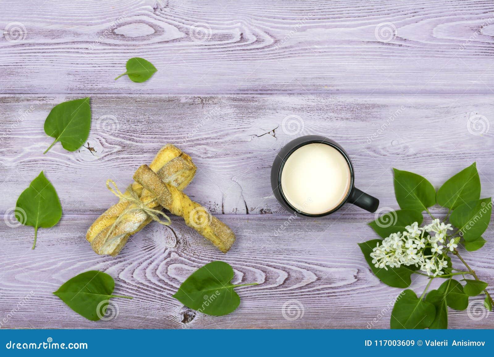 Flache Lage Schwarzer Becher mit Milch Selbst gemachte süße Plätzchen Zweig und weiße lila Blumen auf dem Tisch