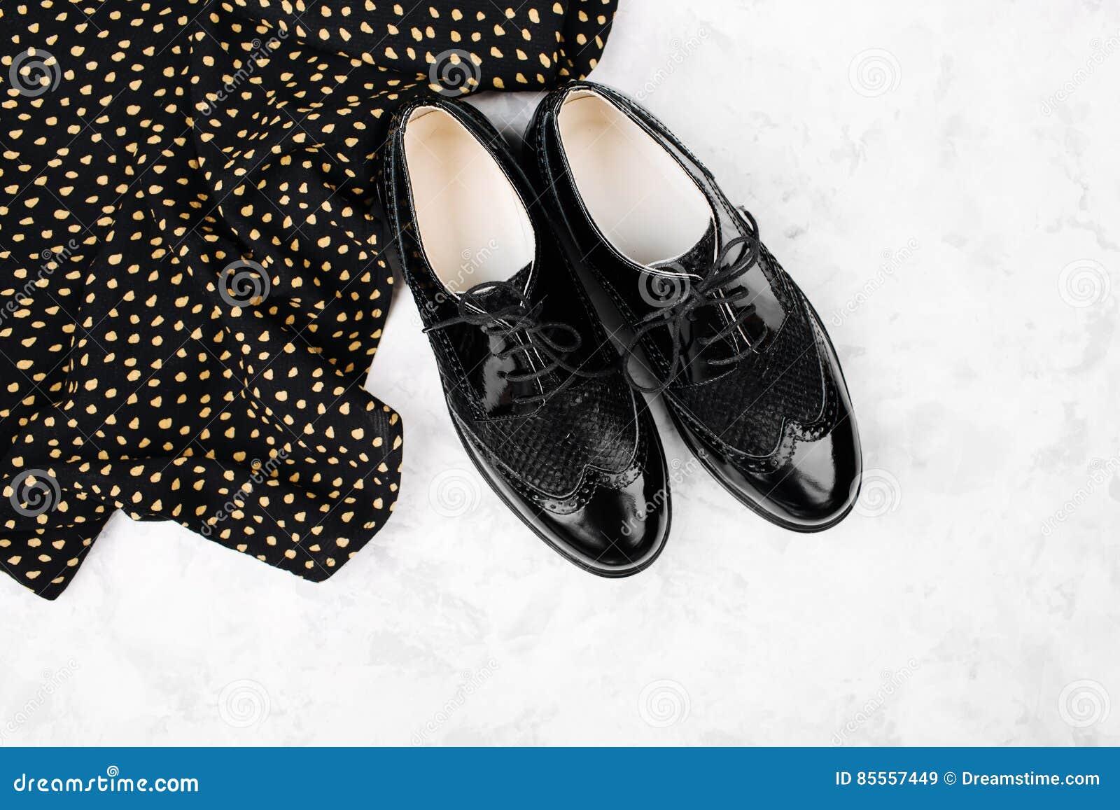 Flache Lageart des Frühlinges oder der schwarzen Schuhe und der Kleidung des Herbstes mit Tupfen