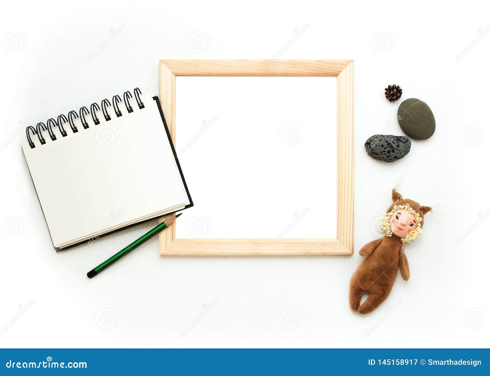 Flacher gelegter Spott oben, Draufsicht, Holzrahmen, Spielzeugeichhörnchen, Bleistift, Notizblock, Steine Innenplan, quadratisch