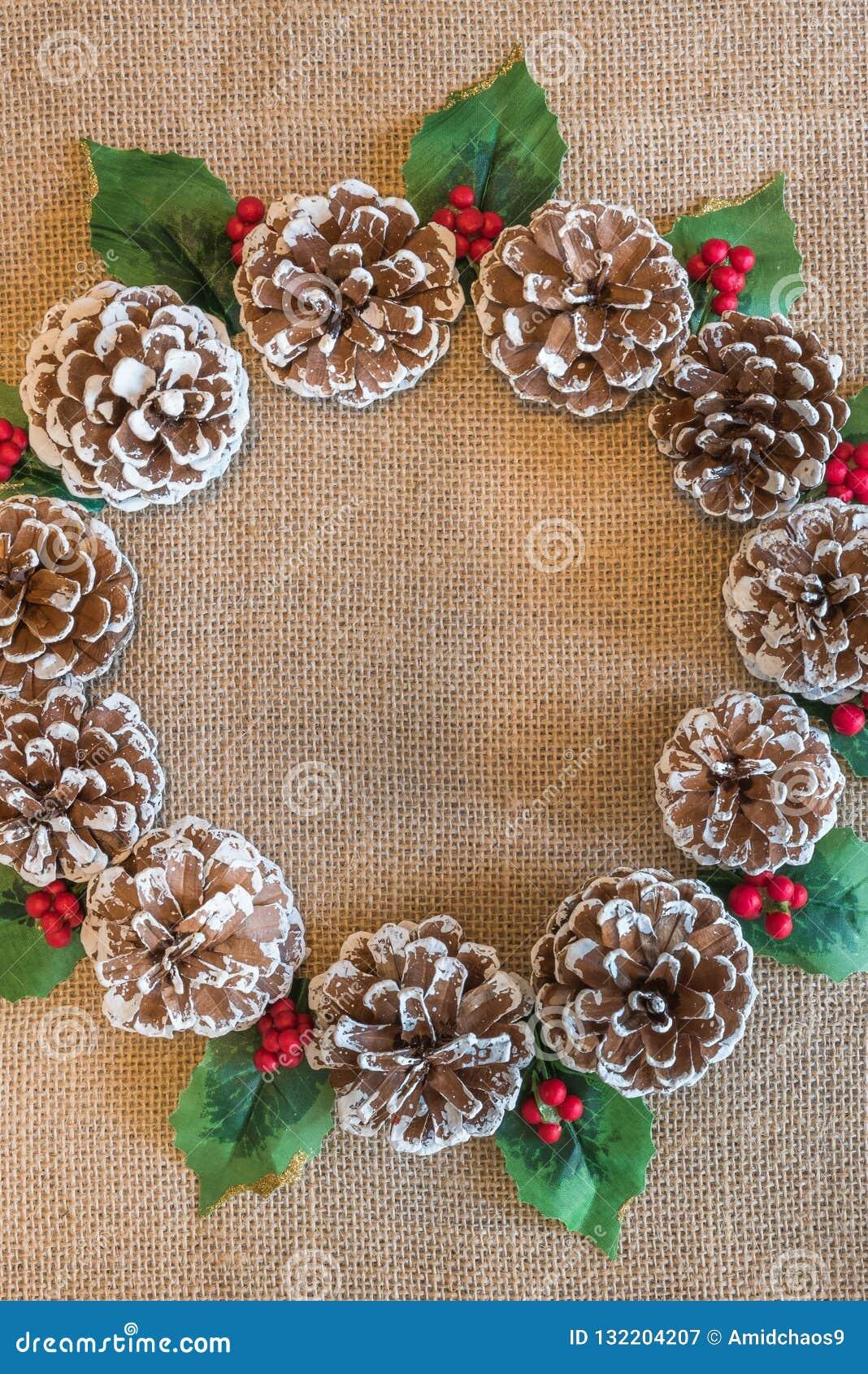 Flacher gelegter Weihnachtskranz von pinecones, von roten Beeren und von Stechpalmenblättern