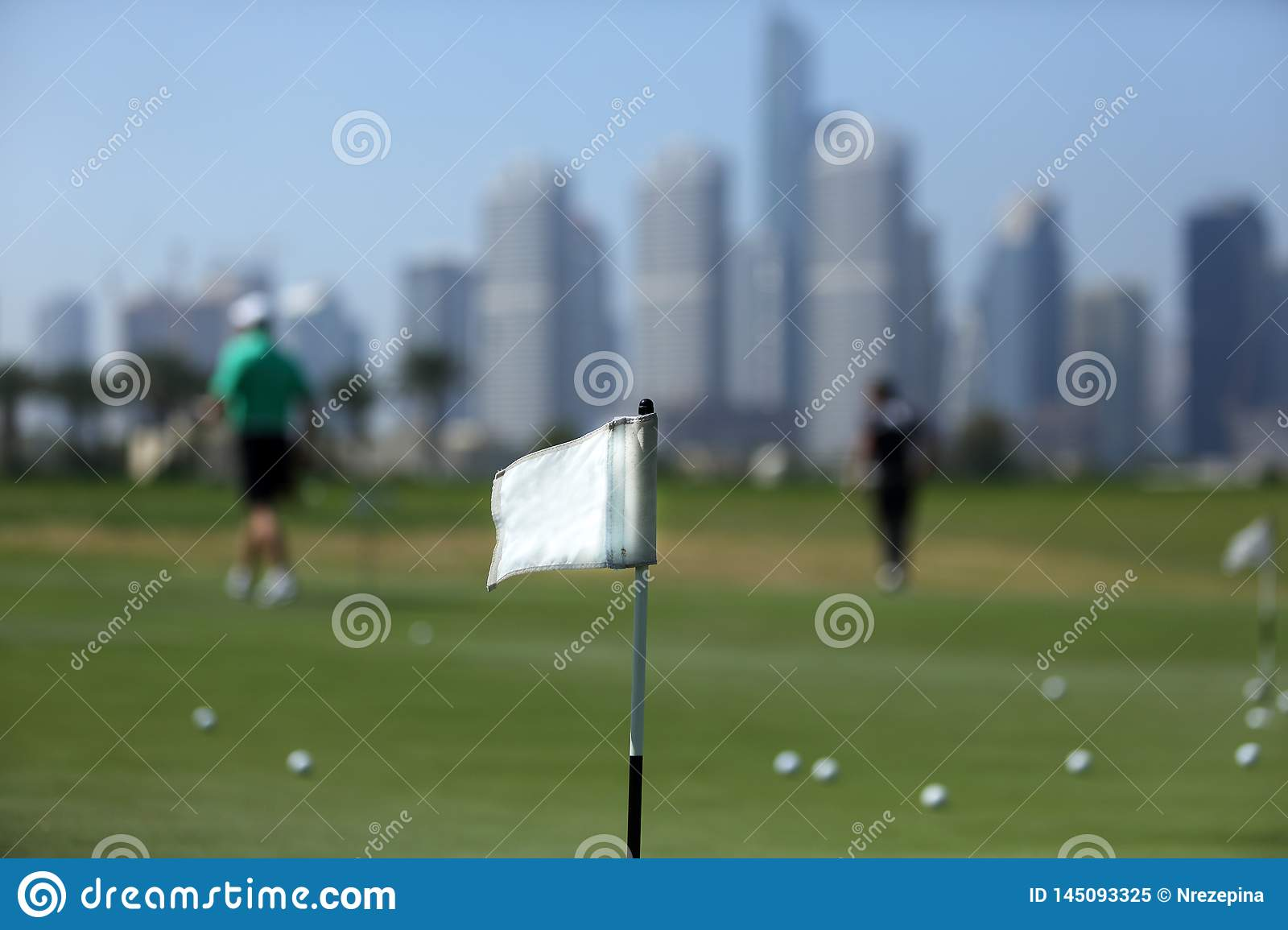 A flag on golf course amid golfers and skyscrapers in dubai