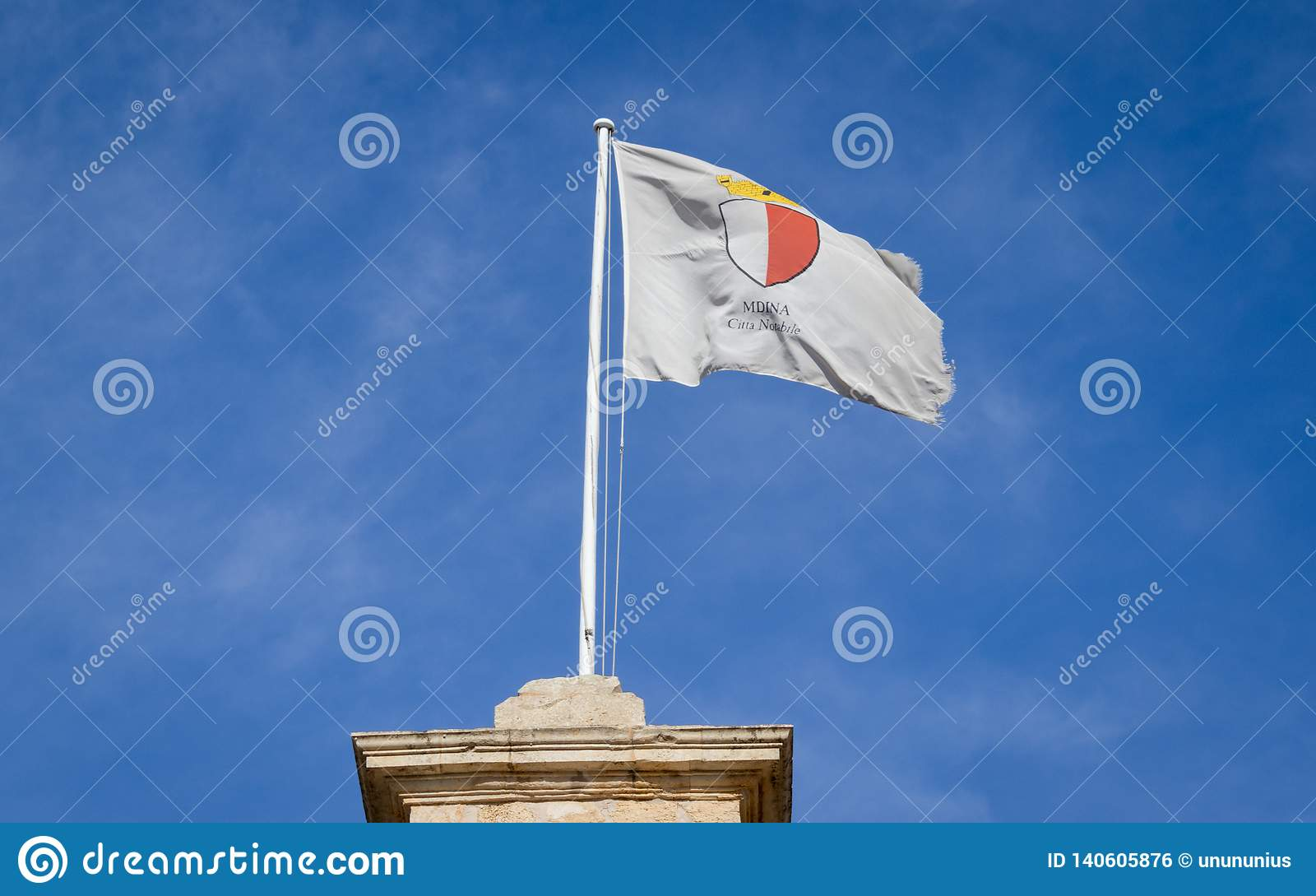 Flag of Mdina City blow in a wind breeze above the Medina Gate in Central Malta on the old historical castle